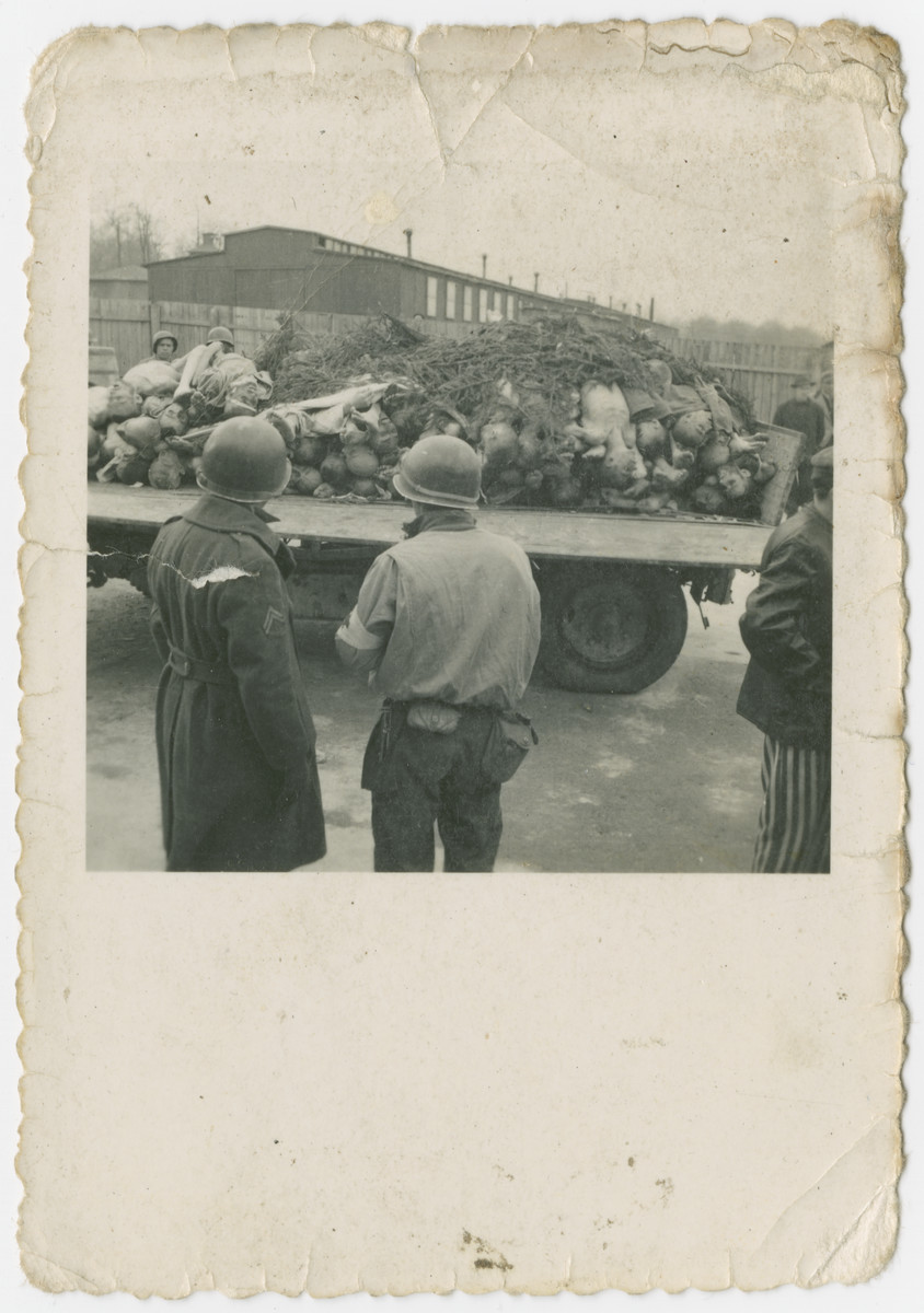 American soldiers watch as the bodies of victims are hauled away on a flat bed truck.