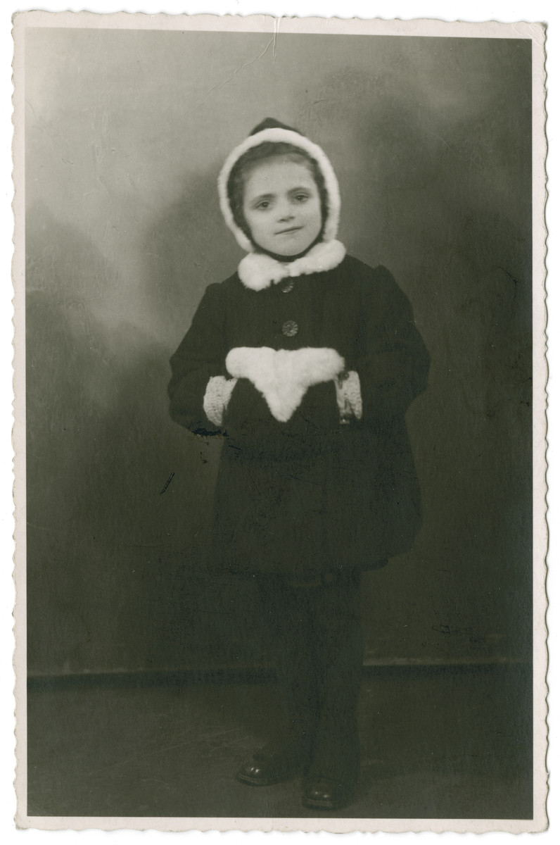 Studio portrait of Janina Nebel with a muff taken while she was in hiding with the Navrodska family.