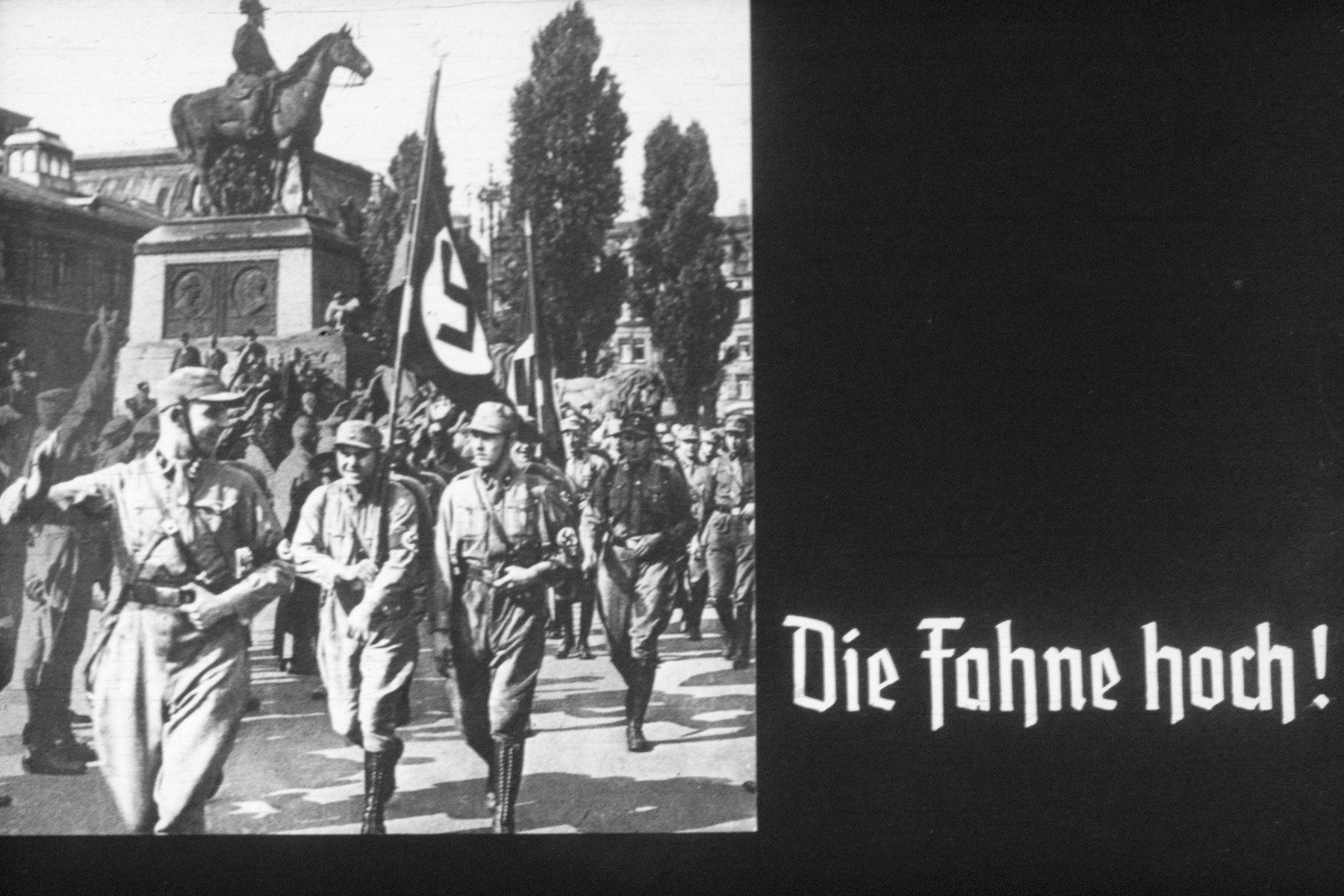 12th slide from a Hitler Youth slideshow about the aftermath of WWI, Versailles, how it was overcome and the rise of Nazism.  Die Fahne hoch!  // The flag is high!