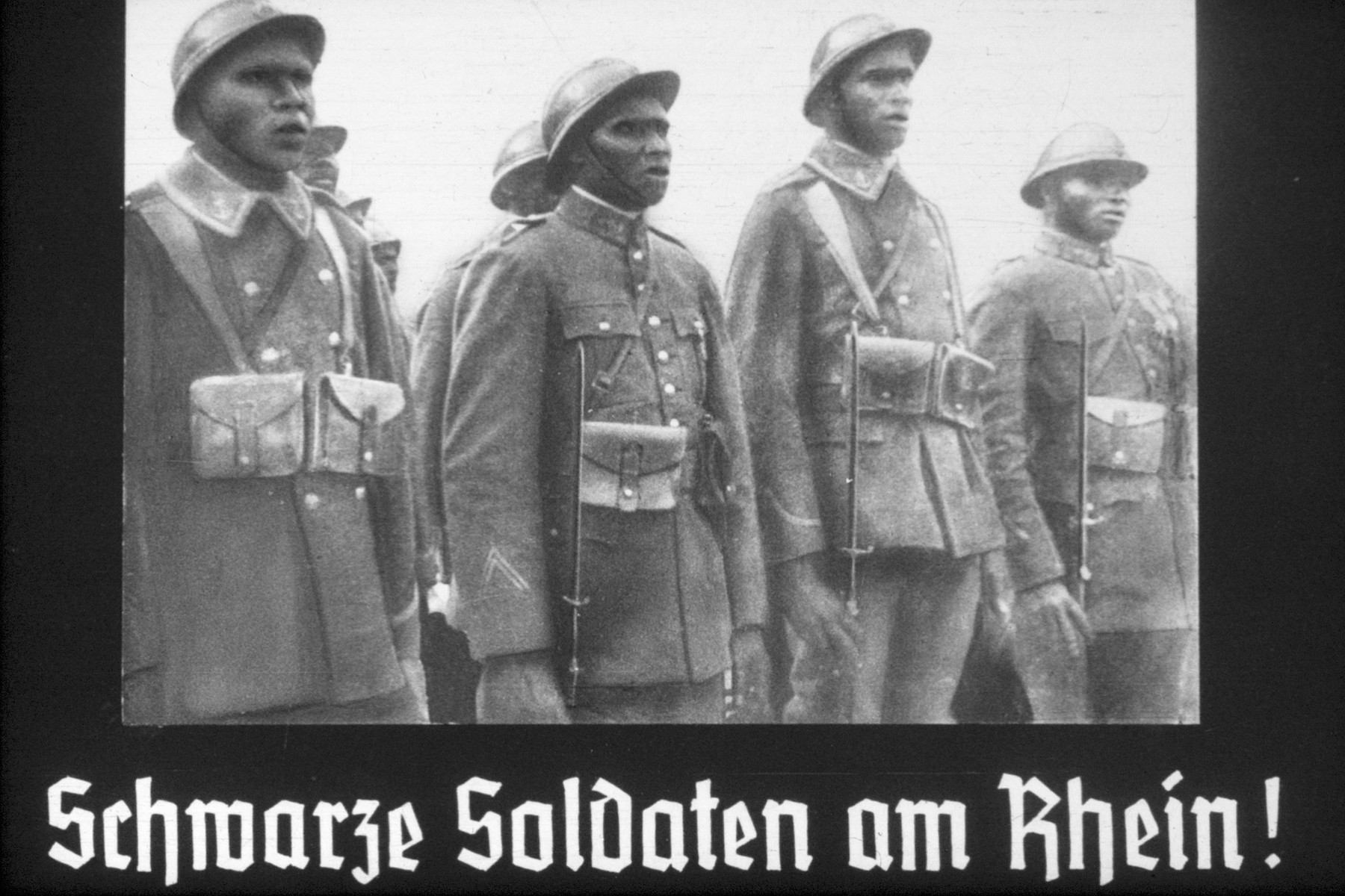 22th slide from a Hitler Youth slideshow about the aftermath of WWI, Versailles, how it was overcome and the rise of Nazism.  Schwarze Soldaten am Rhein! // Black soldiers on the Rhine!