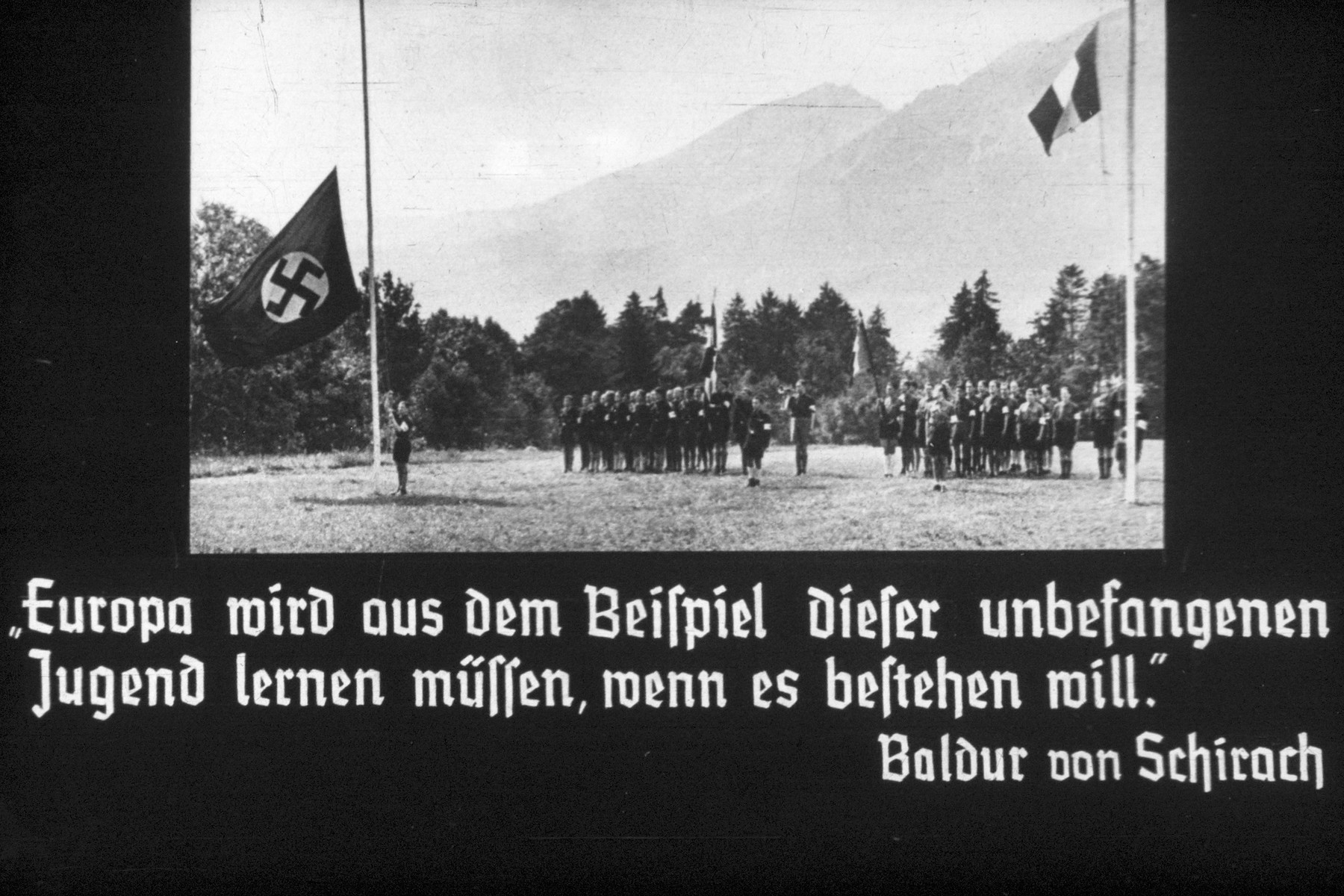 "1st slide from a Hitler Youth slideshow about the aftermath of WWI, Versailles, how it was overcome and the rise of Nazism.  Slide shows a flag raising of the Hitler Youth. Quotation by Balder von Schirach reads:  ""Europa wird aus dem Beispiel dieser unbefangenen Jugend lernen mussen, wenn es bestehen will. ""  ""Europe shall learn from the unprejudiced youth."""