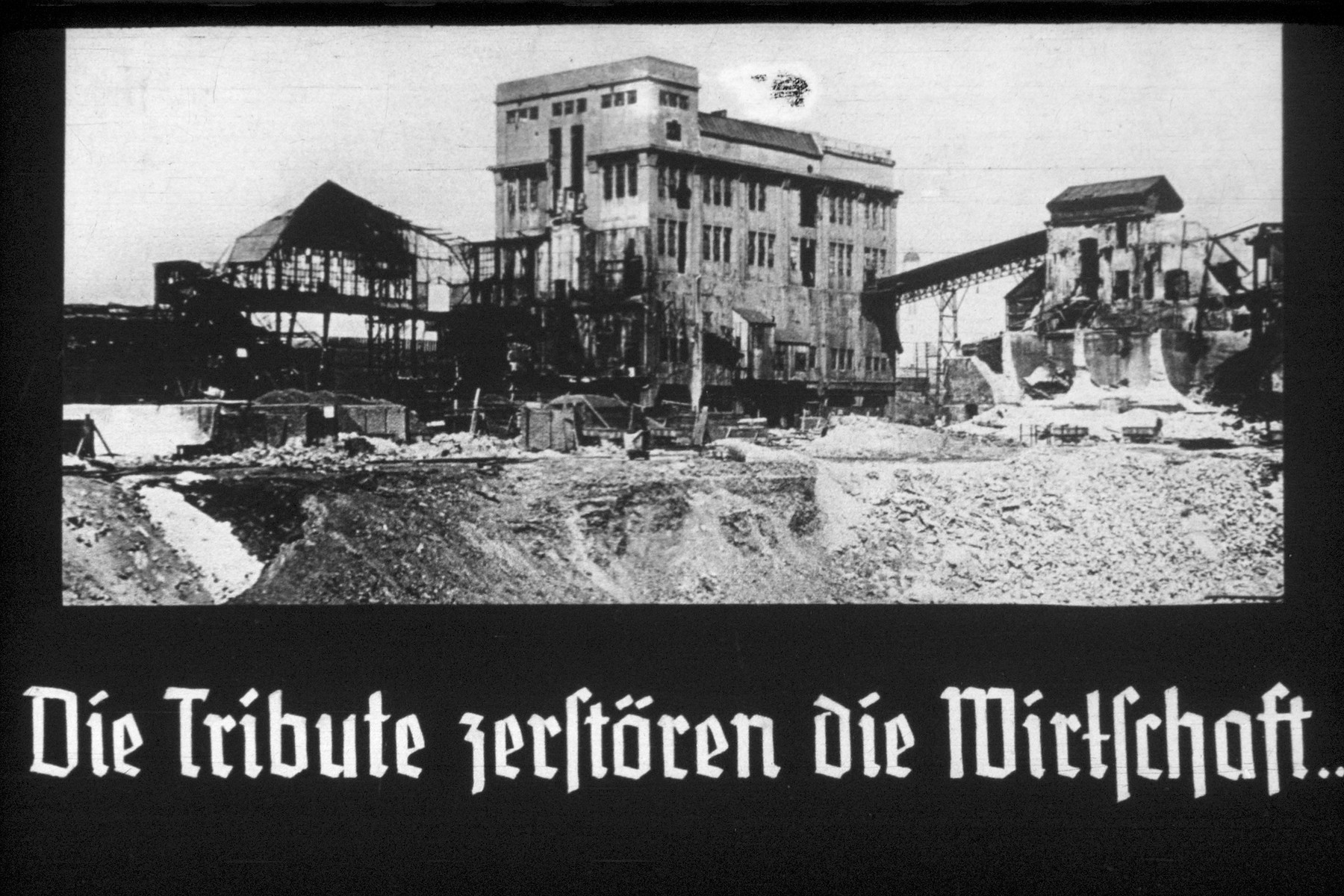 17th slide from a Hitler Youth slideshow about the aftermath of WWI, Versailles, how it was overcome and the rise of Nazism.  Die Tribute zerstören die Wirtschaft // The Tribute destroy the economy.