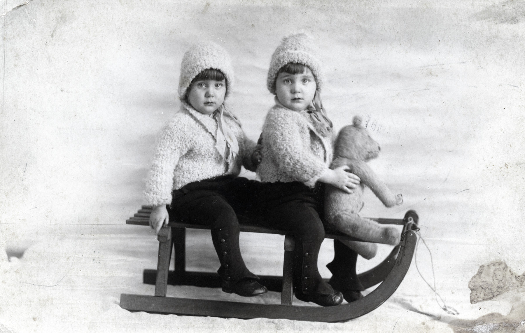 Studio portrait of twins Regina and Ruth Anders sitting on a toy sled with a stuffed bear.