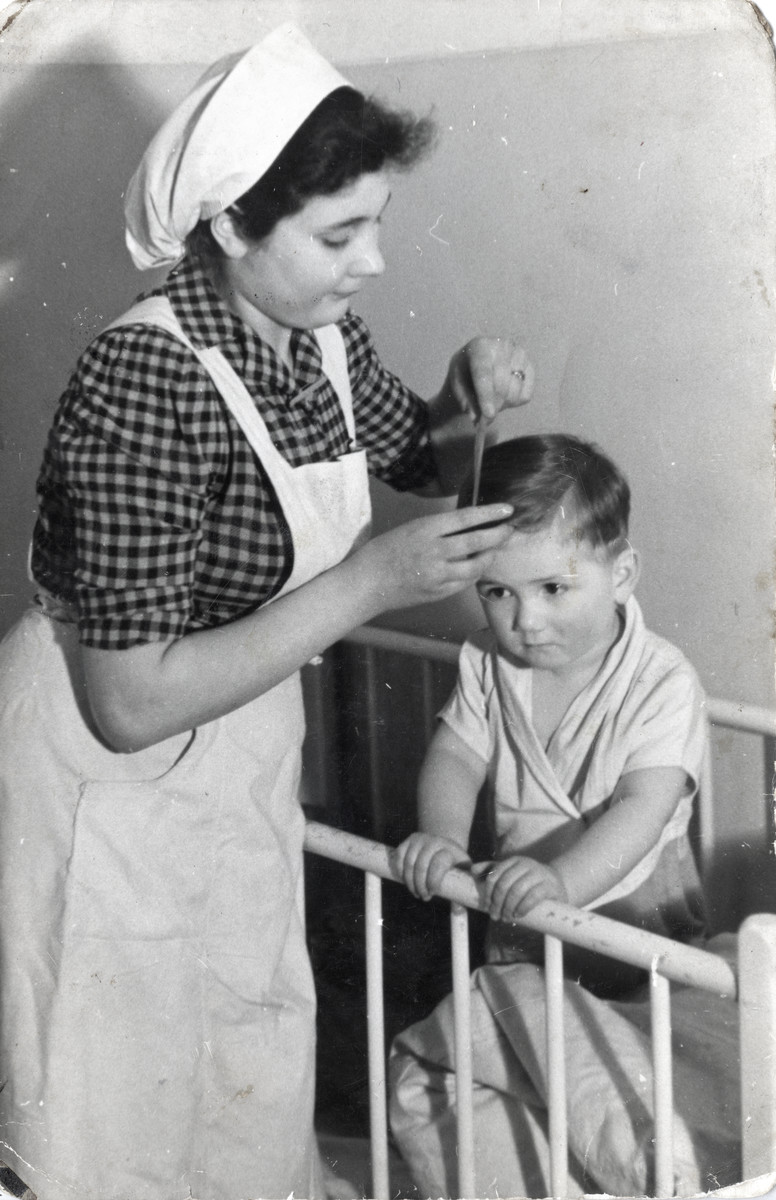 Regina Anders combs the hair of a young boy at a daycare center in postwar Berlin