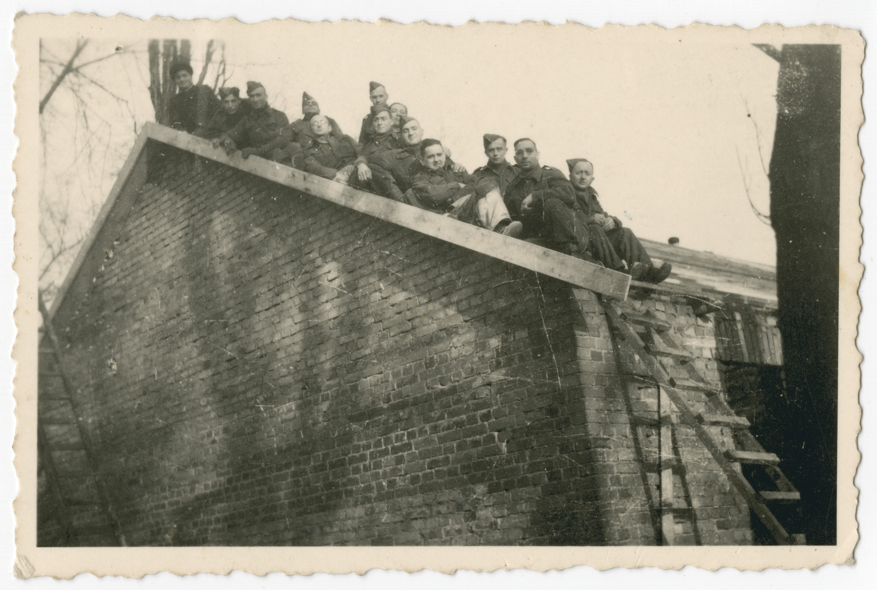 British POWs in Stalag IV A, Elsterhorst pose on the roof of a brick barrack.  Among those pictured is Erich de-Beer, a Germany Jew who immigrated illegally to Palesline and joined the British army.