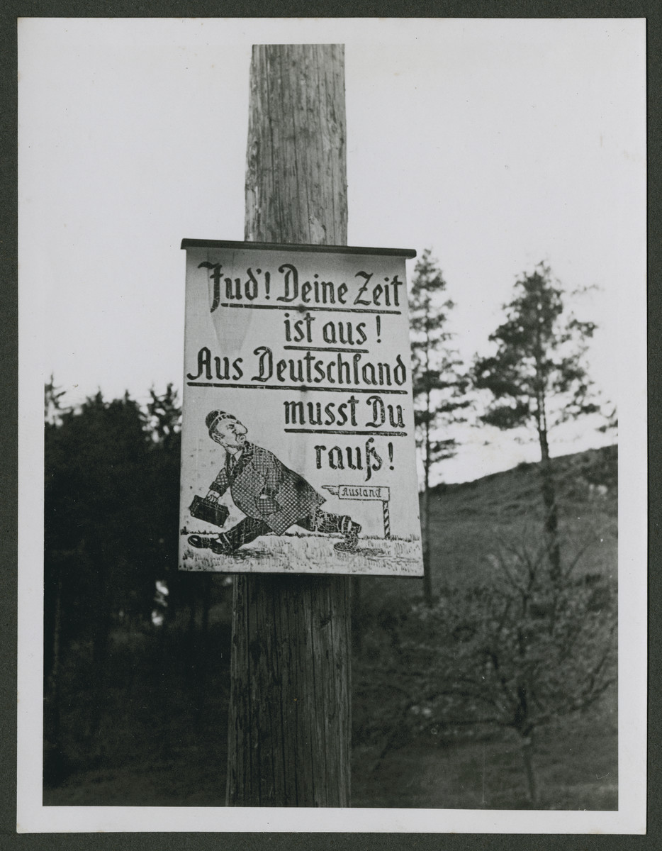 "One photograph from an album of antisemitic signs in Germany.  The sign (in German) reads, ""Jude!  Deine Zeit ist aus!  Aus Deutschland musst Du raus!""   [Jews!  Your time is over!  You have to get out of Germany!]  Below this is  a caricature of a Jew, with sign pointing him to ""Ausland"" [foreign countries]."
