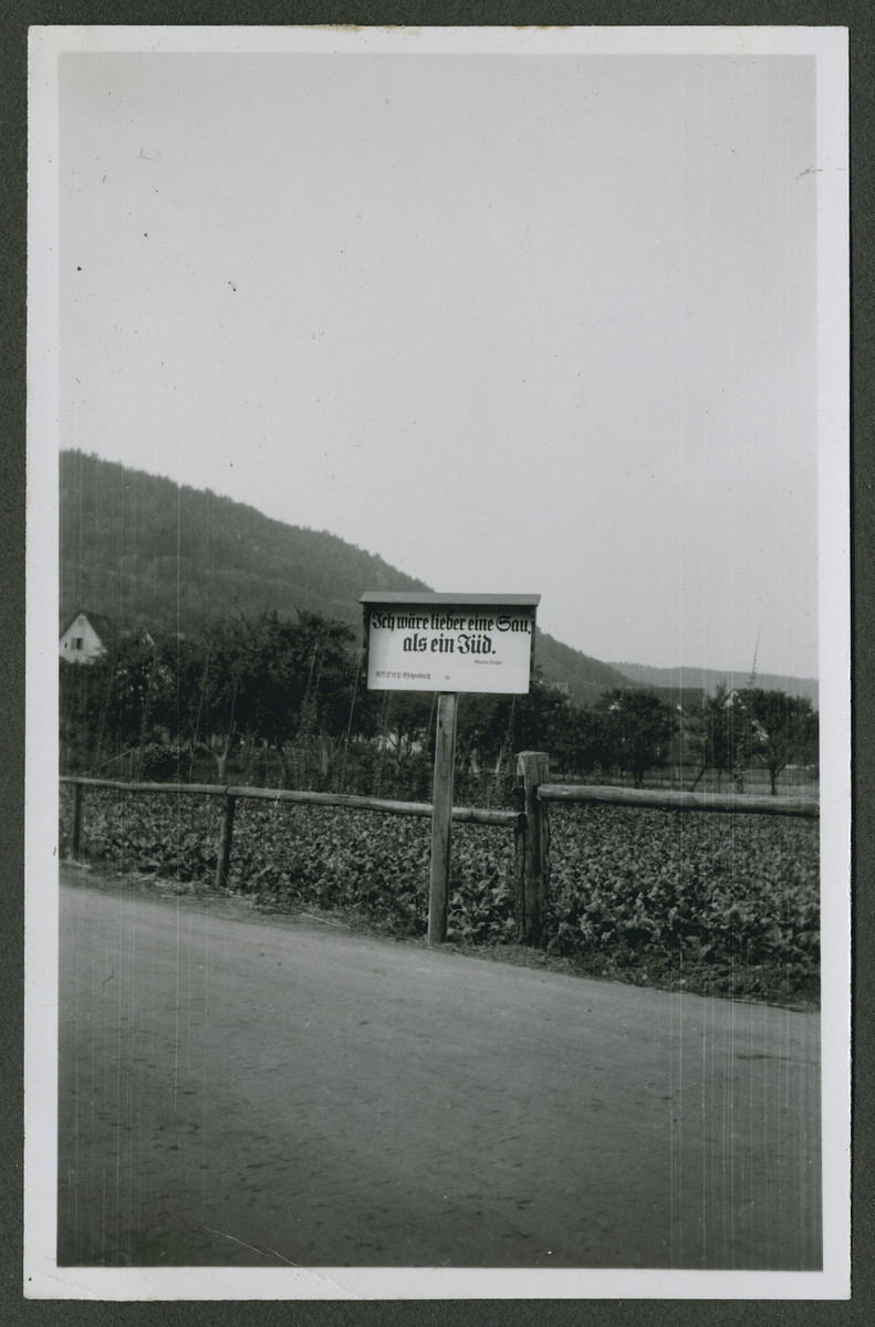 """One photograph from an album of antisemitic signs in Germany.  The sign (in German) reads, """"Ich waere lieber eine sau, als ein Jud. --Martin Luther.  NSDAP Eichenbach.""""  [I would rather be a sow than a Jew.]"""