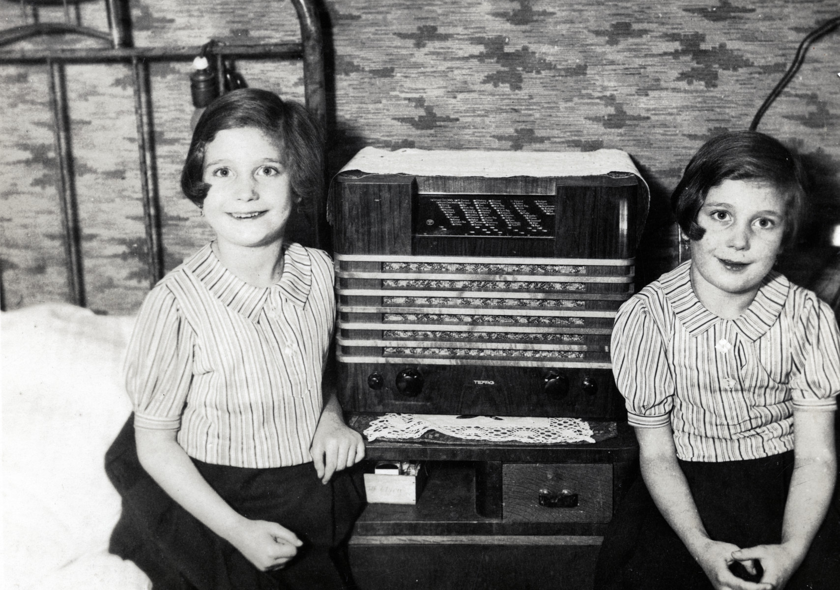 Twins Regina and Ruth Anders sit at home next to their radio.