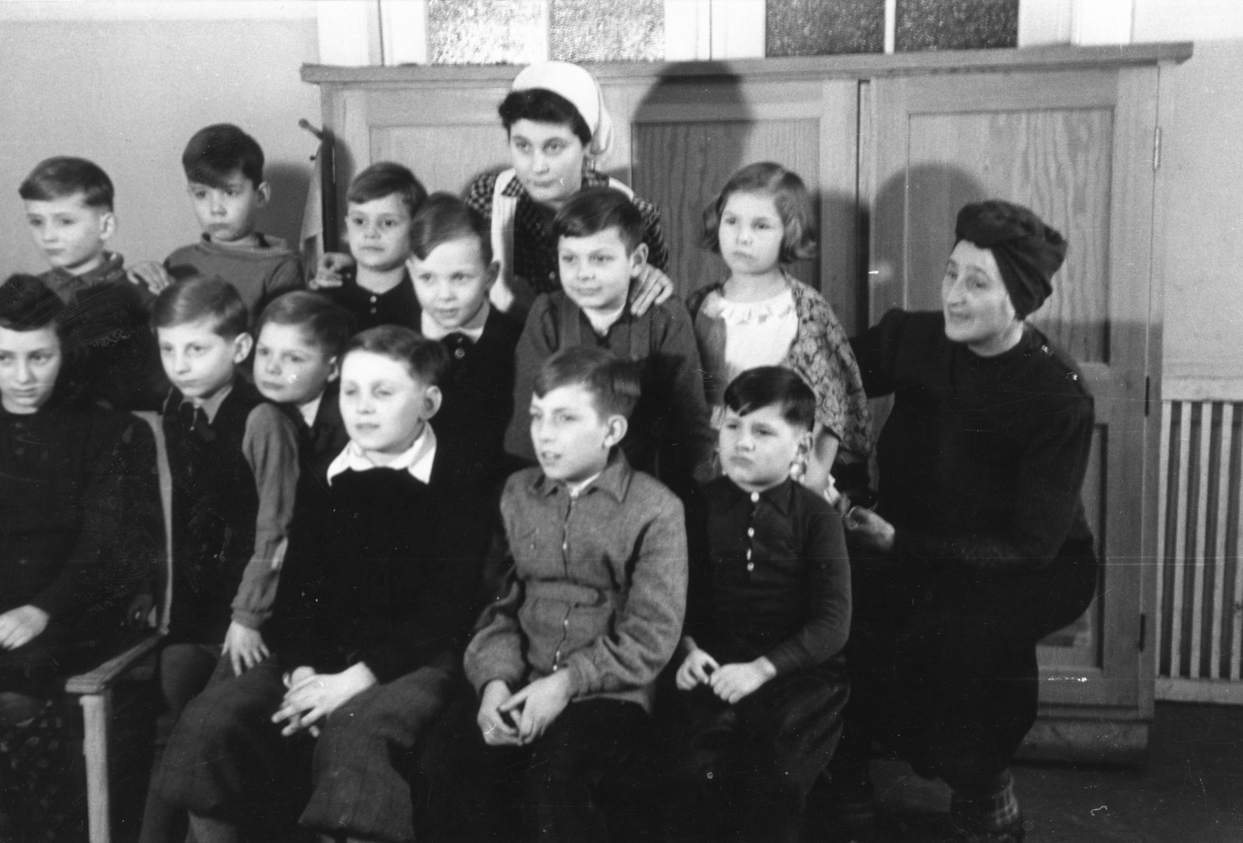 Group portrait of children and caregivers in a postwar children's home in Niedershoenhausen Berlin.  Among those pictured is Regina Anders (top center) and Mrs. Ottowaite (right).