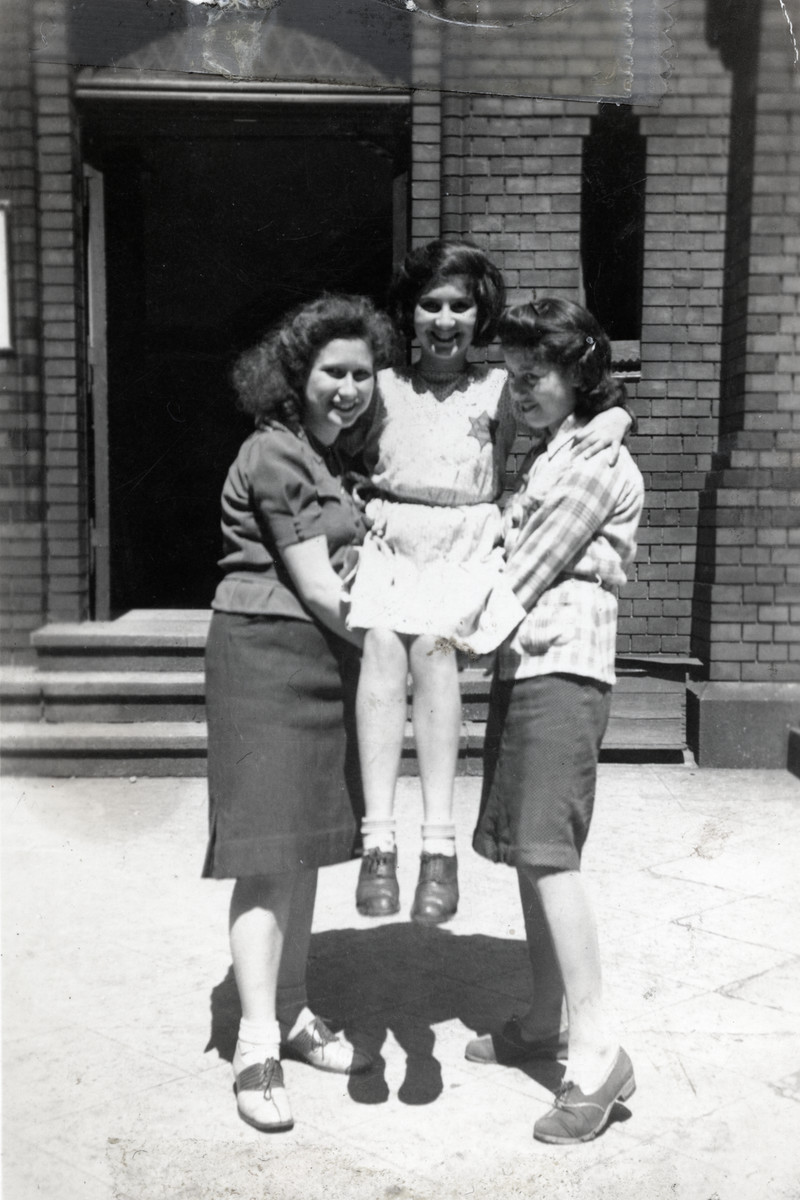 Three Jewish girls, one wearing a Star of David, pose outside the school on Grosse Hamburger Strasse.  Pictured is Sylvia Wagenberg who was later killed in Auschwitz.