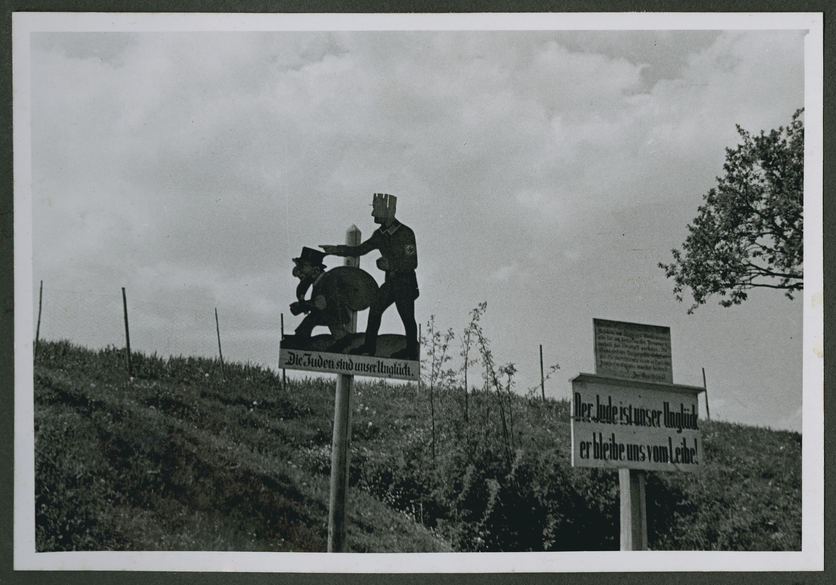 "One photograph from an album of antisemitic signs in Germany.  One sign includes cartoon figures of a Nazi sending a Jew away  and reads  (in German), ""Die Juden sind unser Unglueck.""  [The Jew is our misfortune.]  A second sign (in German) reads, ""Die Juden sind unser Unglueck er bleibe uns vom Leibe!""  [The Jew is our misfortune.  He remains among us at arm's length.]"