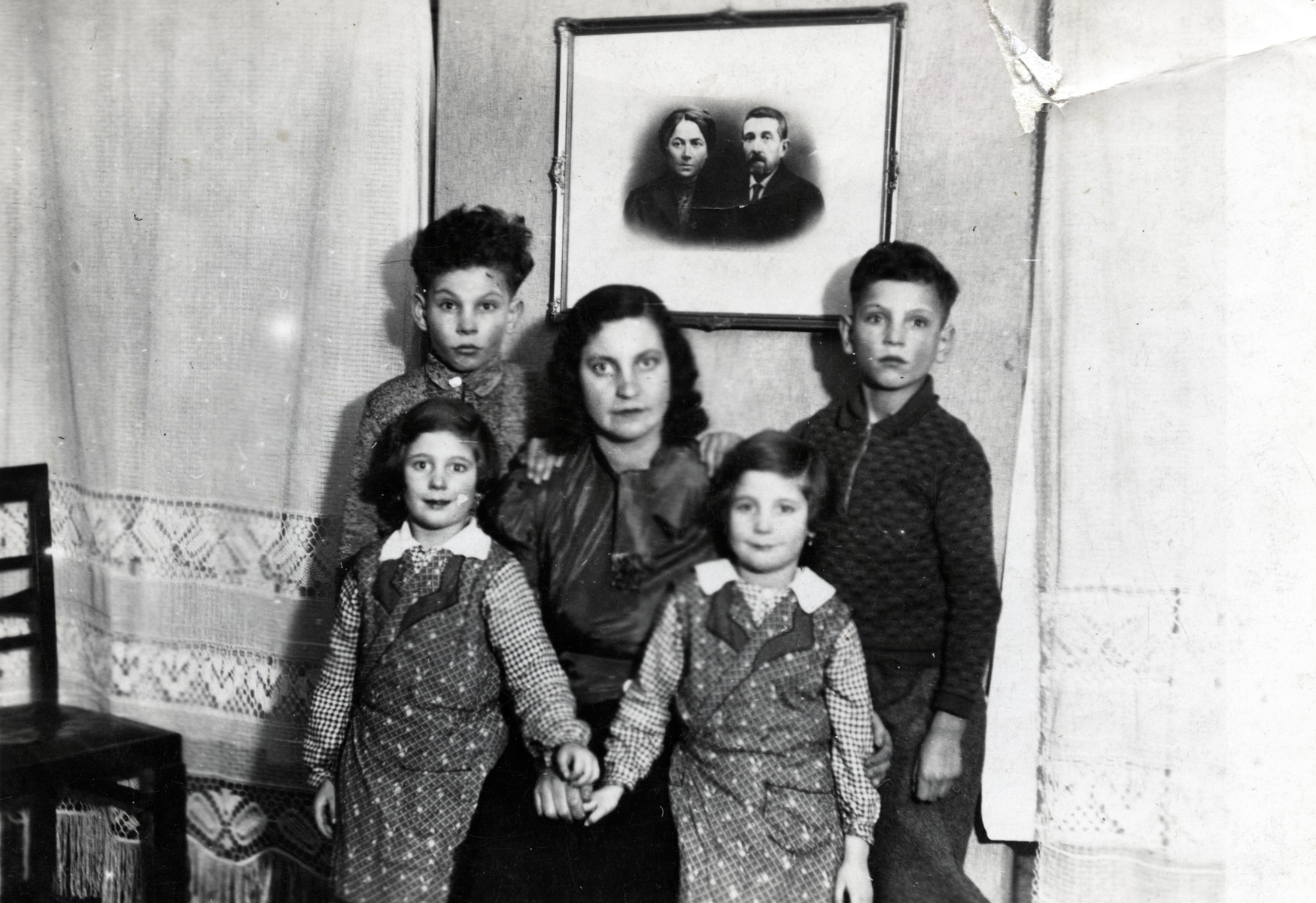 Marta Raifeld Welner poses with her four children in her home underneath a photograph of her inlaws.  Pictured are Benno Raifeld (right) and Theo Raifeld (left). Martha Anders Raifeld is in the center, and her twins Regina and Ruth are in front.