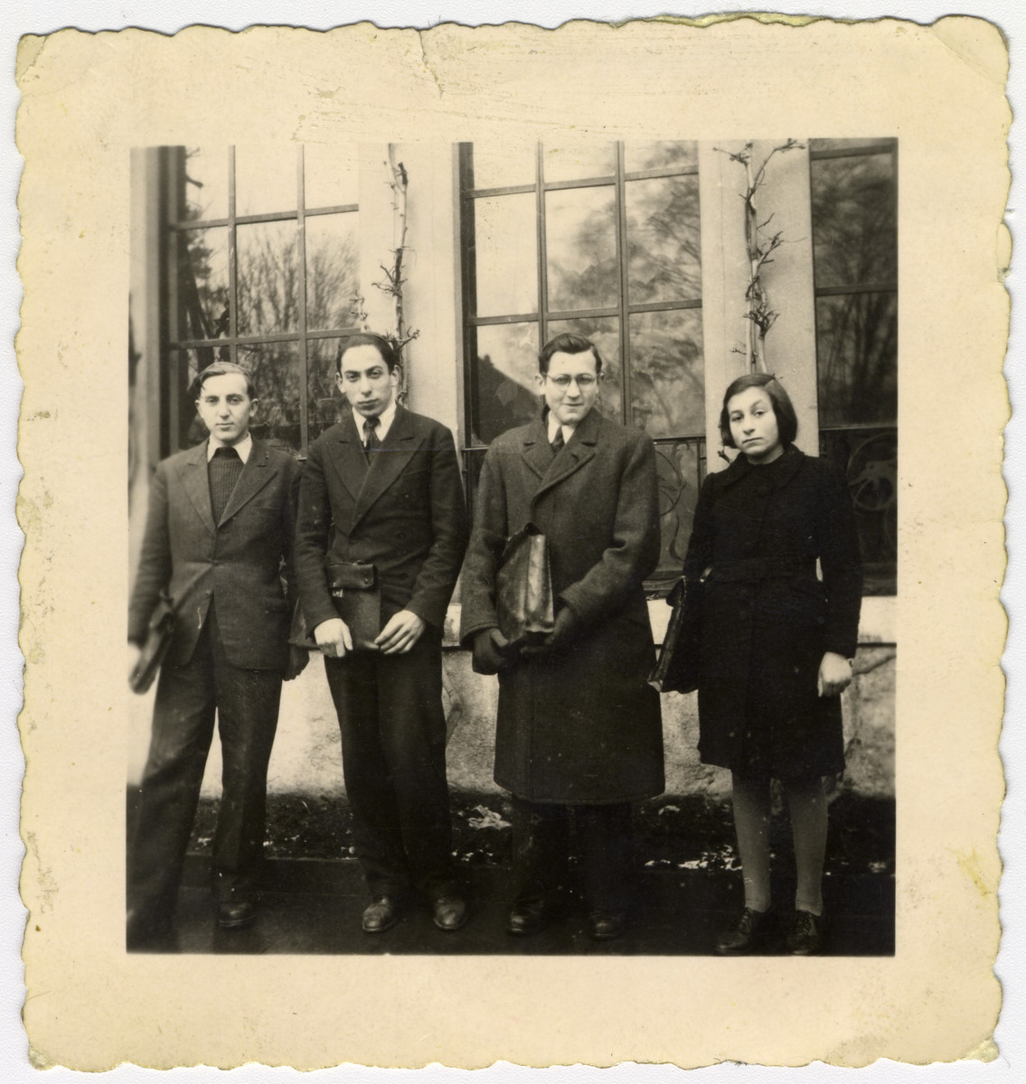Group portrait of four students from Dr. Stern's children's home; they attended local schools.  Ruth Schwarzhaupt stands at the right along with Ernst Sternfels at her left.