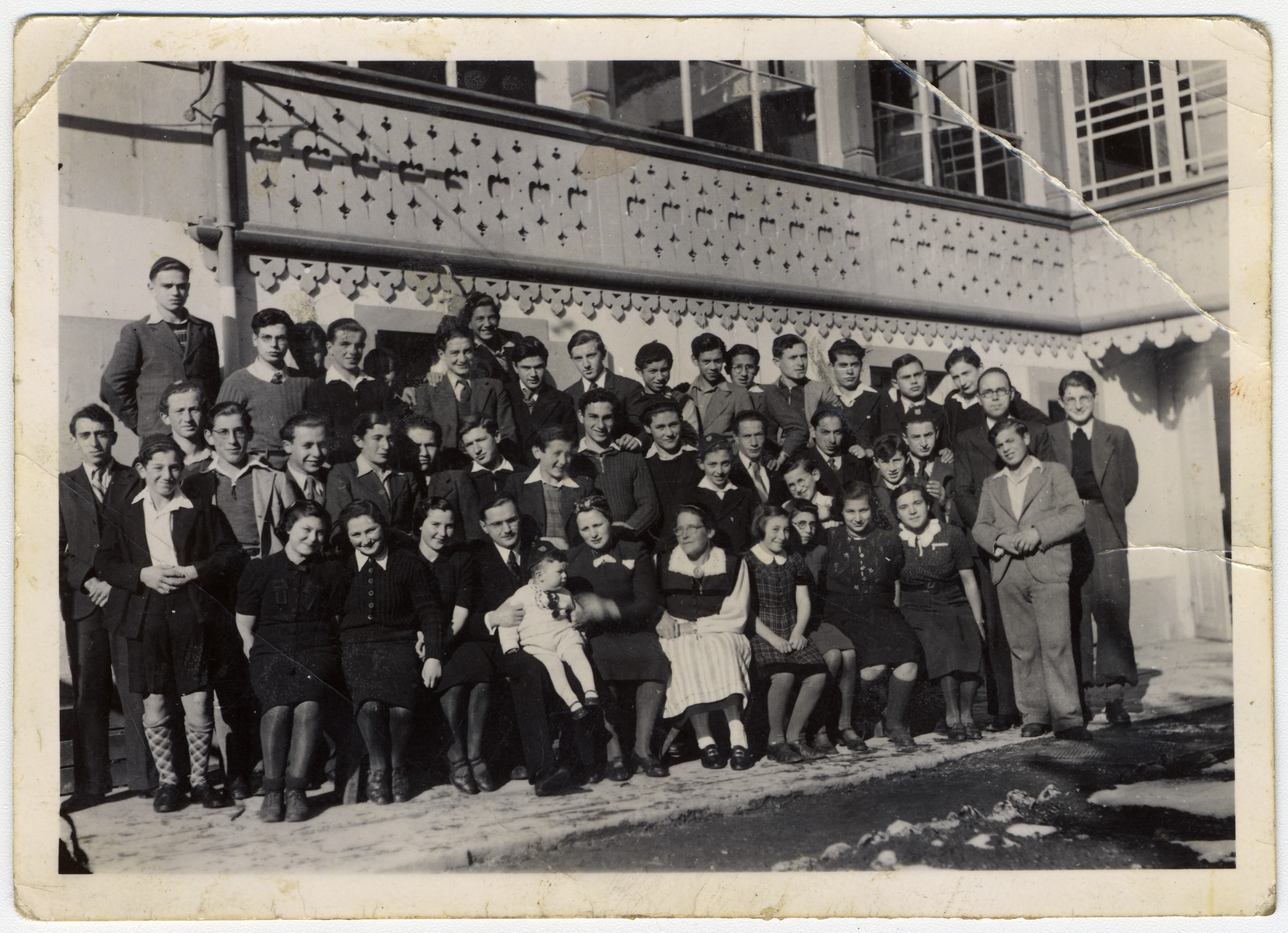 Group portrait of residents of an Orthodox children's home in Basel.  Rabbi Stern is pictured in the front row, center with his wife.  Next to his wife is Miss Riesner, the sewing teacher.  Ruth is sitting next to Miss Riesner.