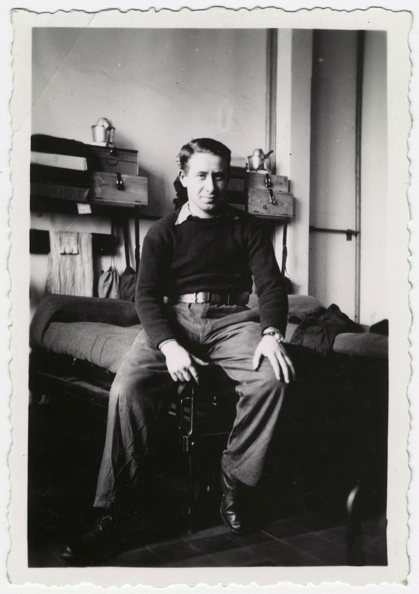 Henri Moskow sits on the edge of his bed.