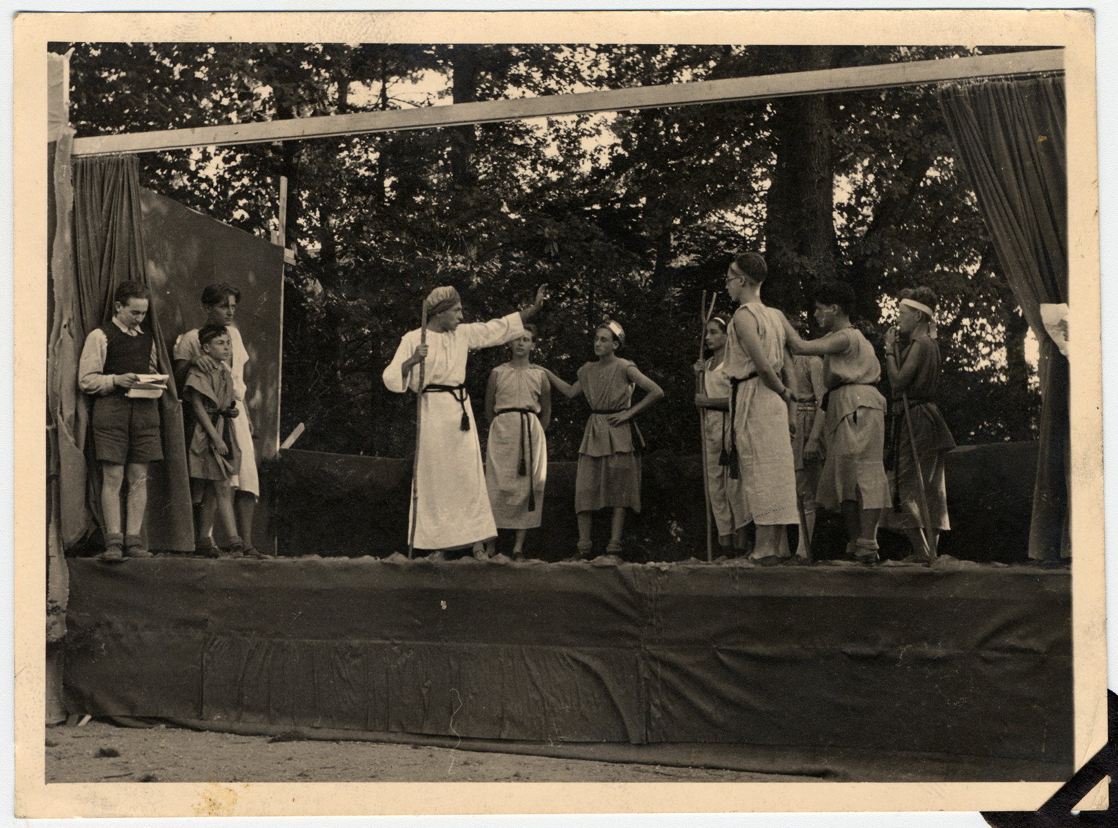 "Refugee children perform a play on a biblical theme in Les Murailles children's home.  Kurt Frost is standing third from the right wearing glasses.  The original caption reads ""treat the strangers like yourselves""."