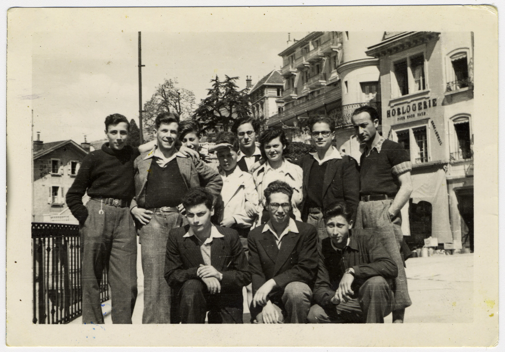 Teenagers from Les Murailles children's homes and members of the  Habonim Zionist youth group pose together on a street in Geneva before leaving as a group for Palestine.  Kneeling from left to right: Yehouda Tuteur, Kurt Frost, Kurt Heilbronner. Standing from left to right: Natan Alter, Ludwig Mayer David Bergmann, Adina Simon,  Manfred Filipson and unidentified  Last row: standing from left to right:  Werner Heilbronner (half hidden between Ludwig Mayer  and David Bergmann) and  unidentified between David and Adina Simon.
