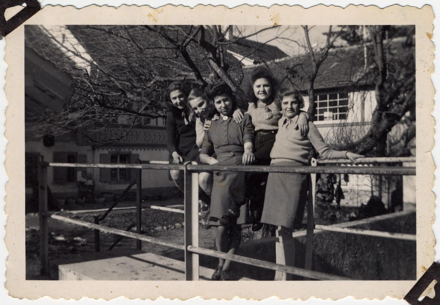 Female teenage Jewish refugees pose together outside in Langenbruck Switzerland.  In the middle is Mrs. Marx, their teacher.