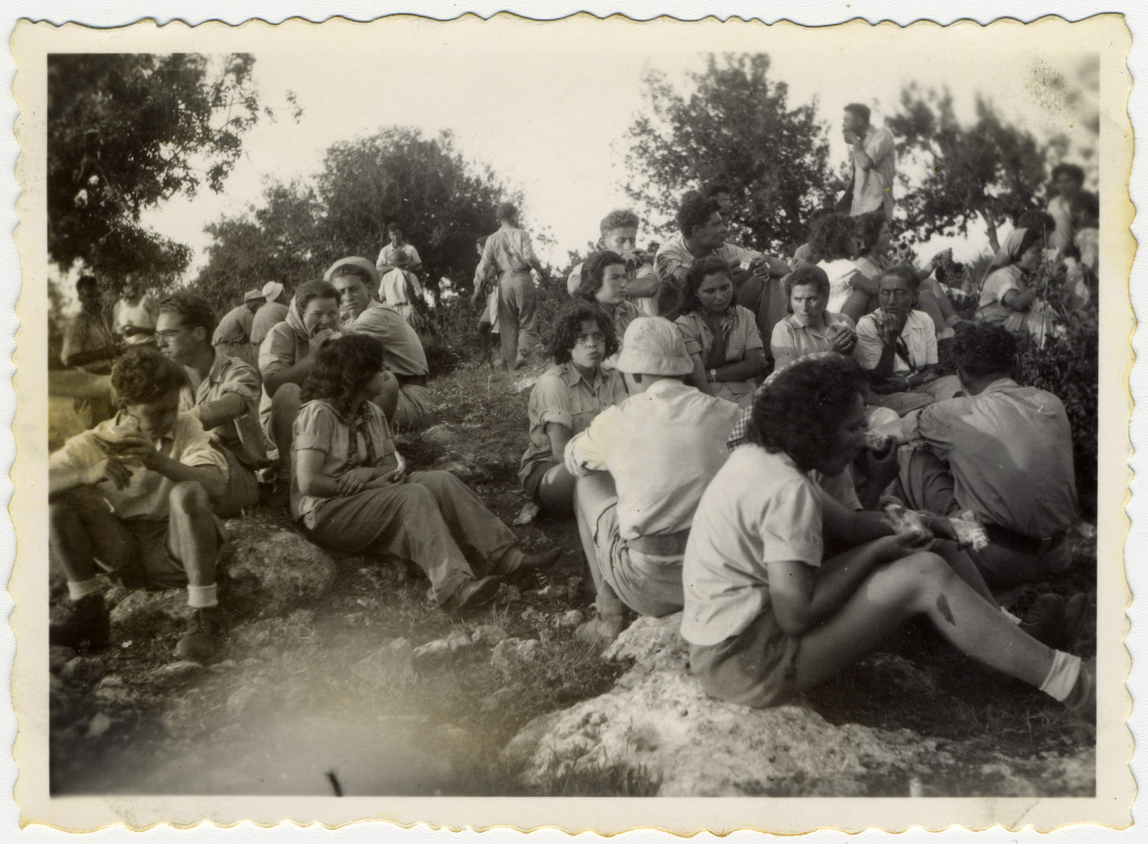 New settlers in Kibbutz Yiftach eat their first lunch outside after the establishment of the kibbutz since the dining room had still not been built.  Pictured on the far left wearing glasses is Mordechay (formerly Kurt) Frost.