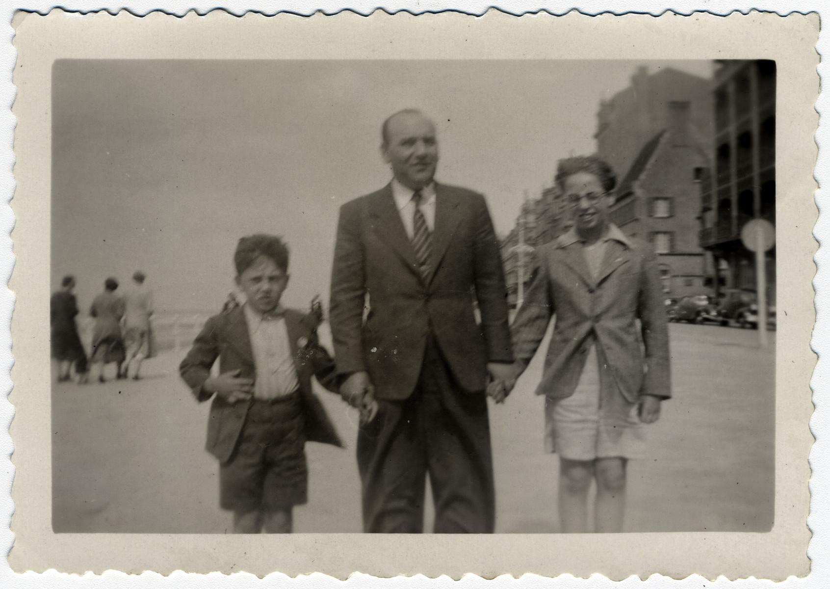 Kurt Frost, an Austrian Jewish boy who came to Belgium on a Kindertransport, walks down the street with his foster family.  From left to right are Henri Korn, his father and Kurt Frost.