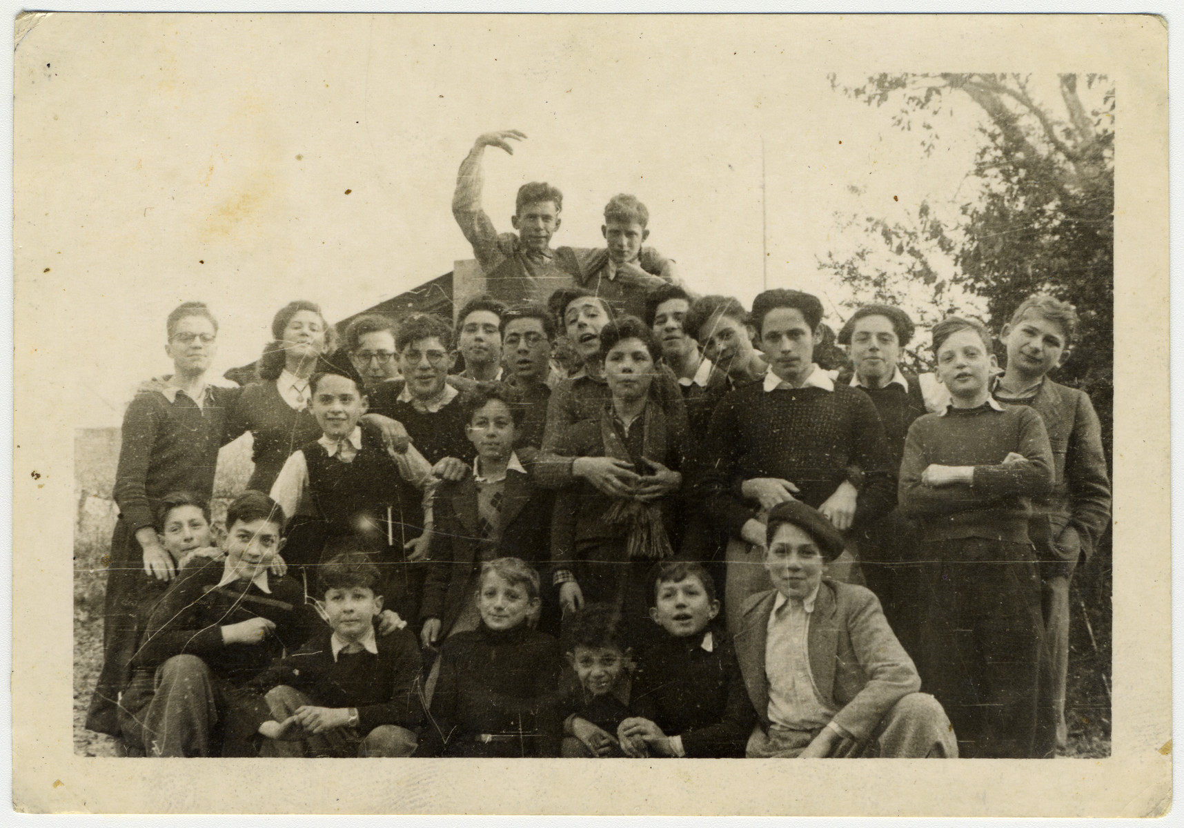 Group portrait of Jewish refugee children in Les Murailles children's home in Geneva.  Among those pictured are Manfred Filipson (standing on the left with glasses), Theo Brenig (middle), Alex Alter (next to him), David Bergman, Otto Weiner (right), Ludwig Meier (back left), Simon Nudel (standing fourth from right), amd Tuvia Hirsch (third from right).