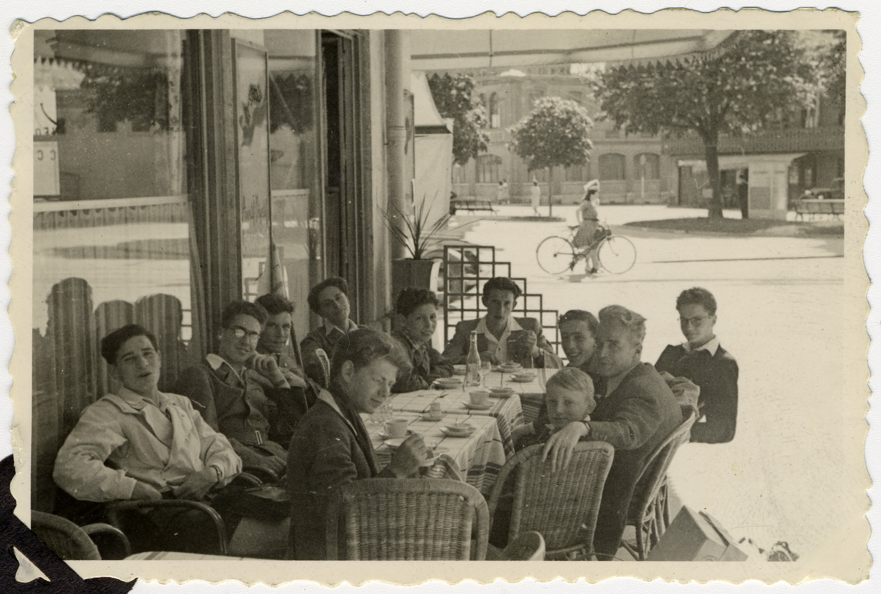 Teenagers from Les Murailles children's home eat a final ice cream in an outdoor cafe in Geneva prior to leaving Switzerland on Youth Aliya.  Pictured on the left are Otto Weiner, Kurt Frost, Ludwig Mayer and David (Tuvia) Bregman.  Michel Ashkenazi is at the far  head of the table, and the boys' teacher, Mr. Pugatz is seated in the middle of the right side.