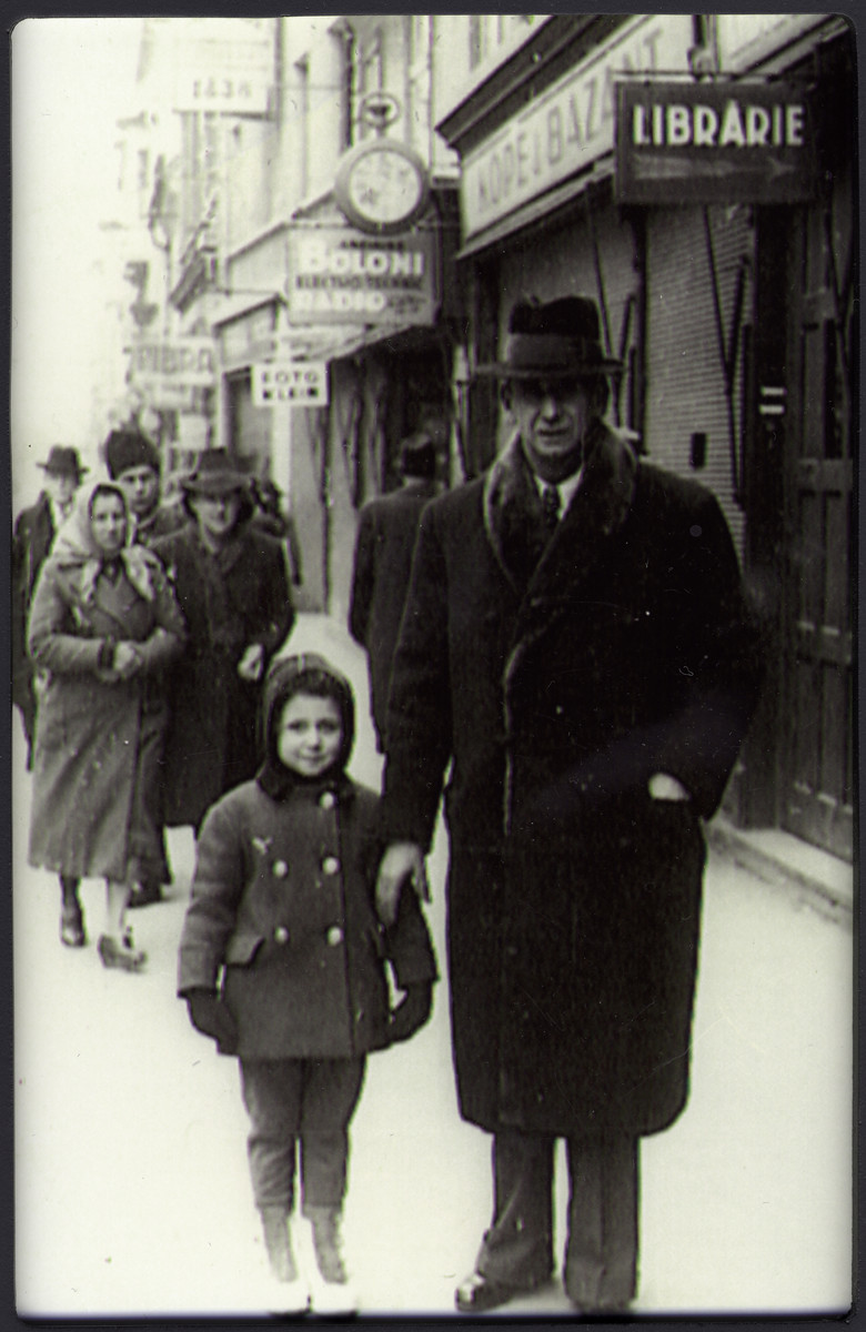 Marcell Jozsef walks down a commercial street in Brasov street with his daughter Agneta.