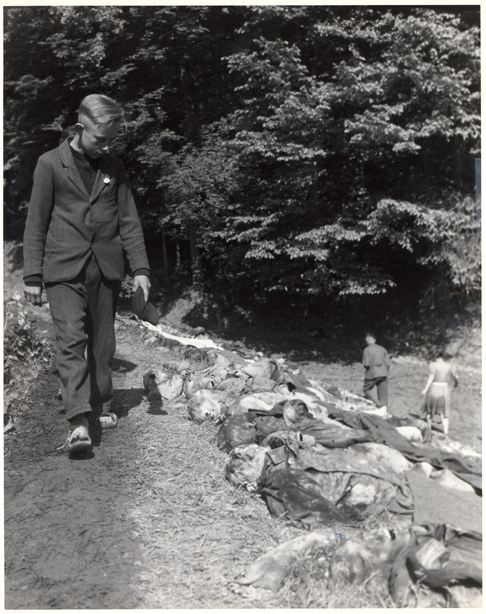A German boy walks past the corpses of bodies of prisoners from the Woebbelin concentration camp.
