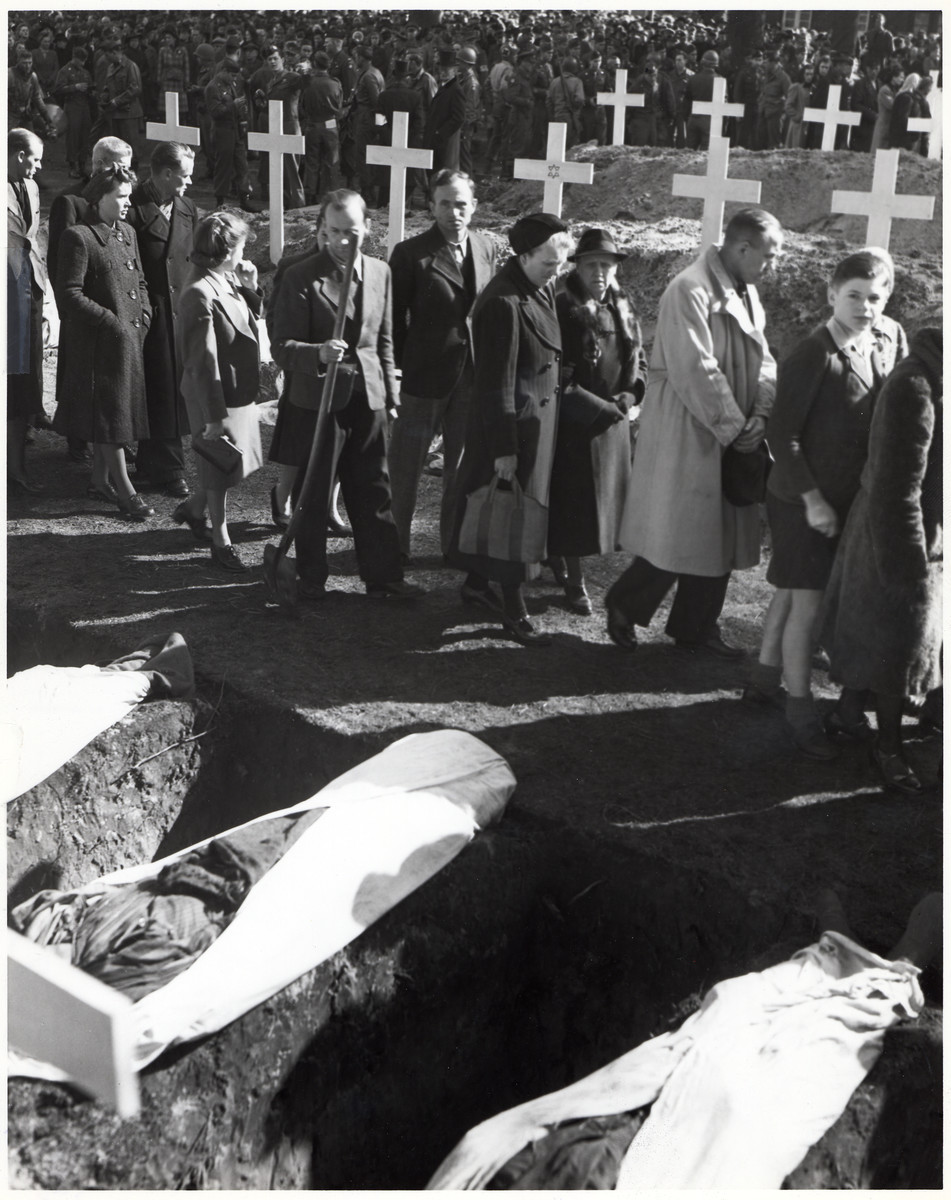 "German civilians are forced to walk past the victims of the Woebbelin atrocity prior to their burial.  The original caption states: ""German civilians of Ludwigslust, Germany, file past the graves of the 200 victims of starvation in the Nazi concentration camp near Wobbelin.  Germans brought the bodies from the camp for burial under the supervision of soldiers of the 82nd Airborne."""