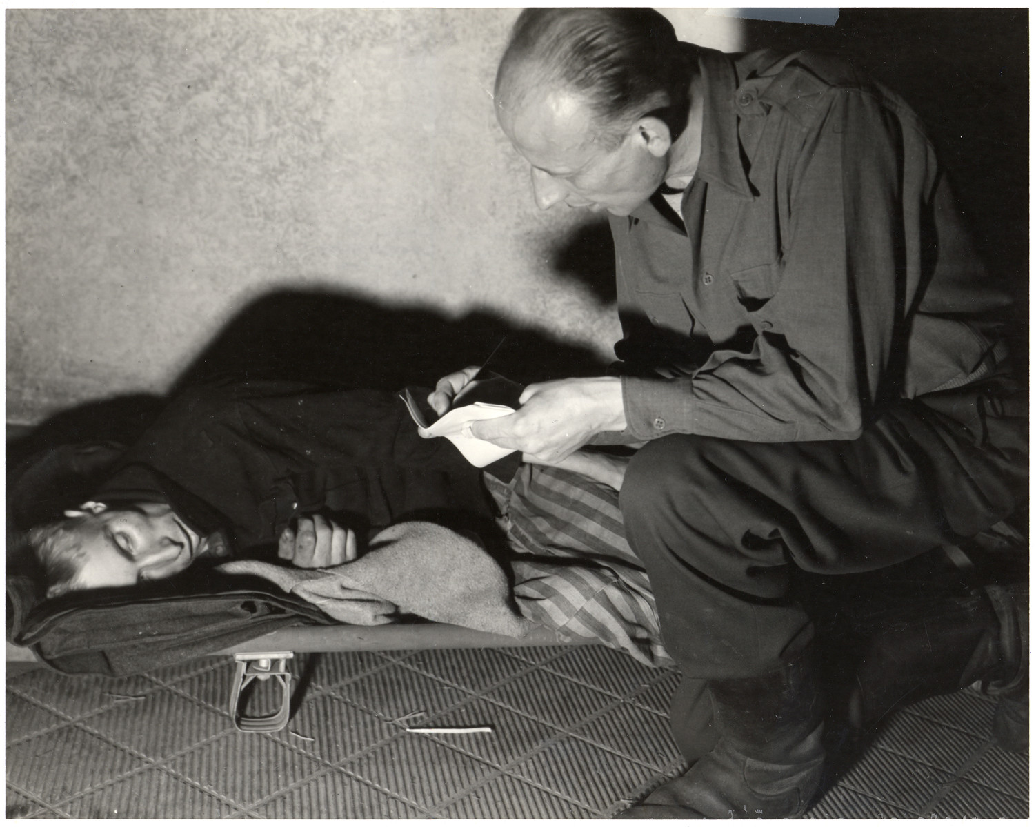 A man kneels next to an enfeebled survivor of the Woebbelin concentration camp and takes notes.