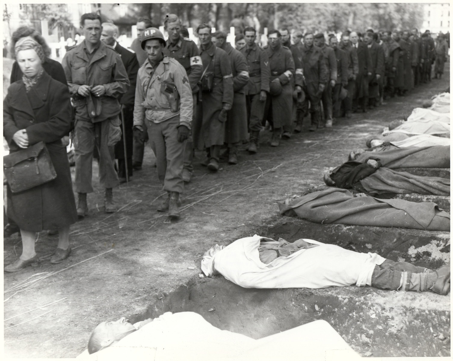"American soldiers force German troops to see the bodies of those who starved to death in Woebbelin.  Original Caption: ""An American MP escorts the line of German soldiers marched past the graves of the Wobbelin concentration camp starvation visctims under the supervision of the 82nd Airborne Division, U.S. Ninth Army, in the town of Ludwigslust, Germany, where graves have been prepared by German civilians. 5/7/45"""