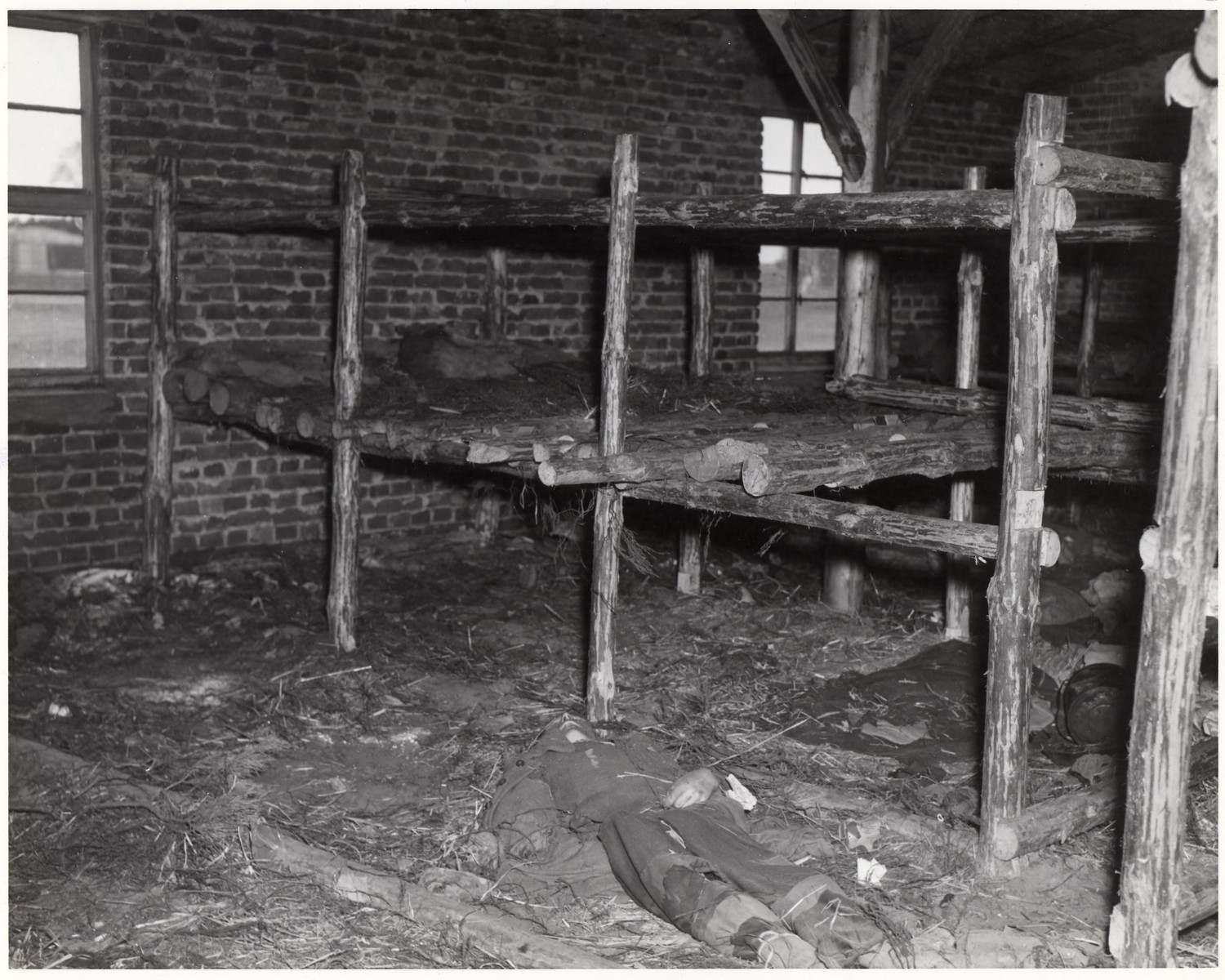 "The body of a starved prisoner lies on the floor of a barrracks of the Woebbelin concentration camp.  The original caption reads:: ""Wobblin Concentration Camp (No.8 of 13 photos).  he camp, recently captured by troops of the U.S. Ninth Army, had many prisoners who starved to death. Here one lies dead on the floor in the living quarters of the prisoners.  82nd Airborne Div., Wobbelin, Germany. 5/4/45.""  Original caption from donated photograph:  ""A dead inmate lies on the floor of one of the filthy ""bedrooms"" of the concentration camp at Webblin.  U.S. troops liberating this atrocity center described it as one of the worst in Germany.  Hundreds of dead prisoners were found piled up in one building and hundreds were discovered in crude, hastily dug pits.  Into one mass grave the Germans had tossed the corpses of 300 slave laborers of various nationalities.  Of the original 4,000 prisoners, it is estimated that 150 died daily, mostly from inhuman treatment and starvation.  German residents of the area were ordered to exhume the bodies and provide respectable burial."""