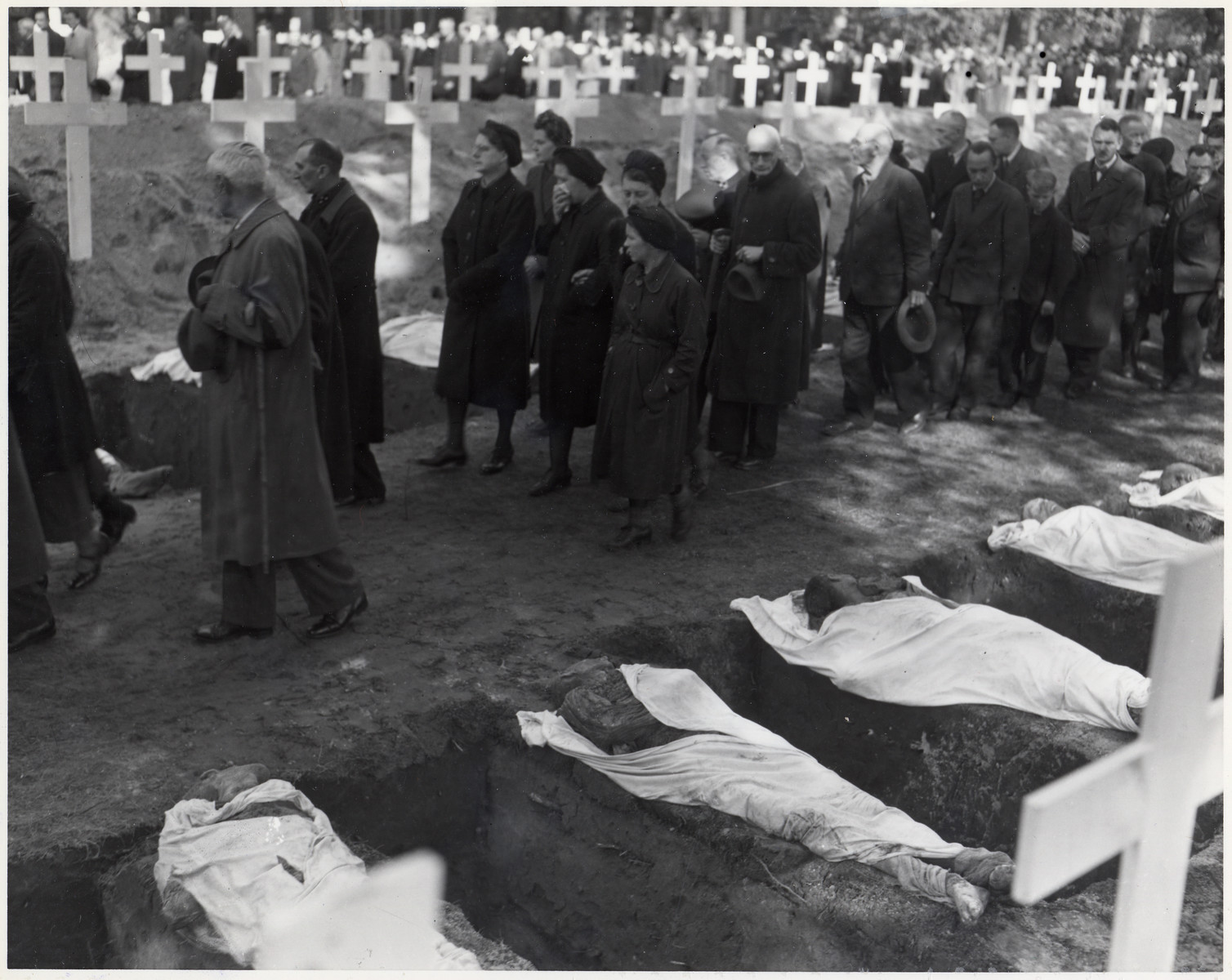 German civilians are forced to walk past the victims of the Woebbelin atrocity prior to their burial.