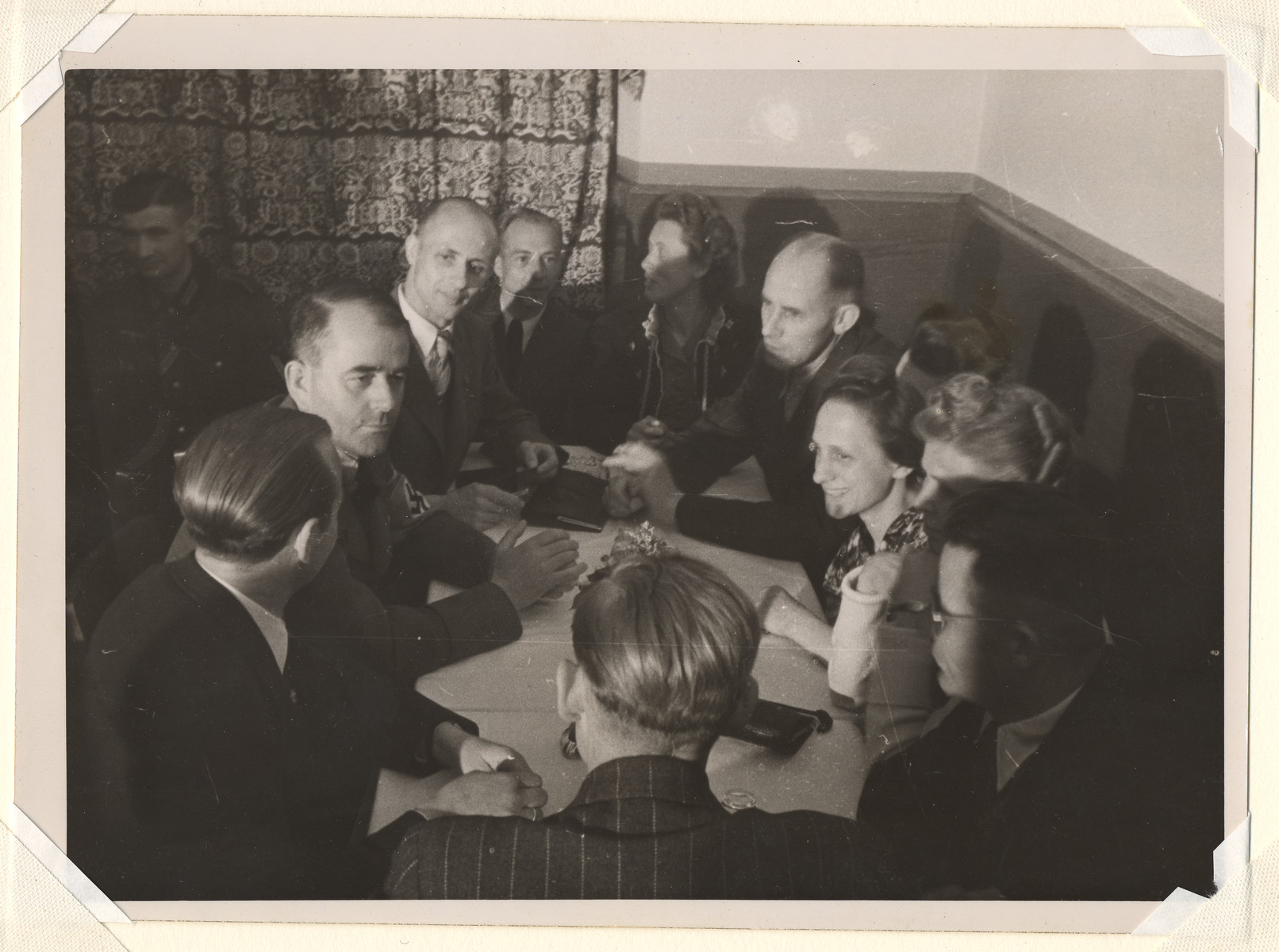 Albert Speer sits around a table with a group of unidentified people.