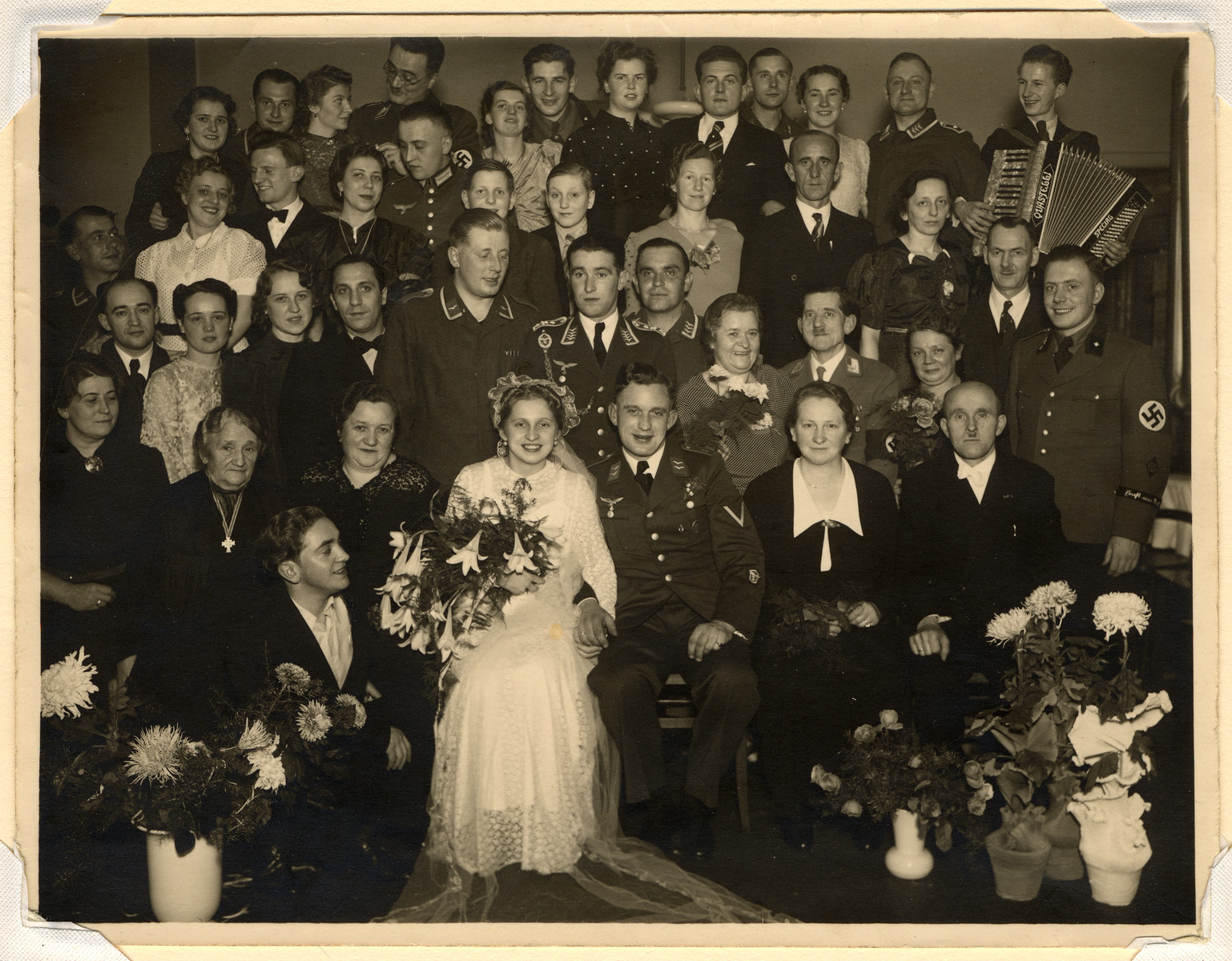 Family portrait taken at the wedding of an SS man.  The woman on the left is wearing a Cross of Honor of the German Mother, an award given to women who contributed to the pure Aryan race by reproducing.  Three levels of medals were awarded:  a bronze was given for four children, silver for six, and gold for eight.