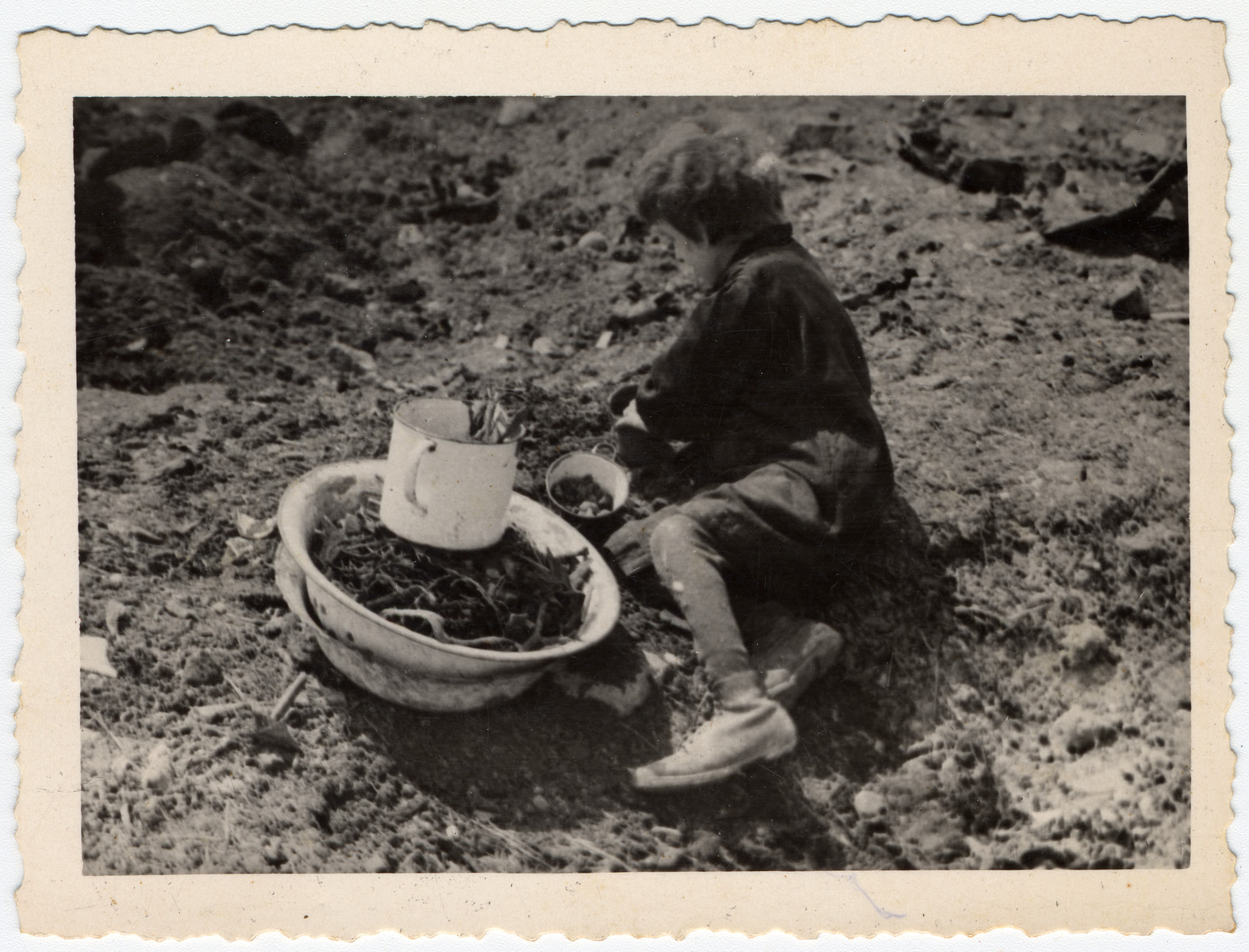 A child gathers scraps of food.