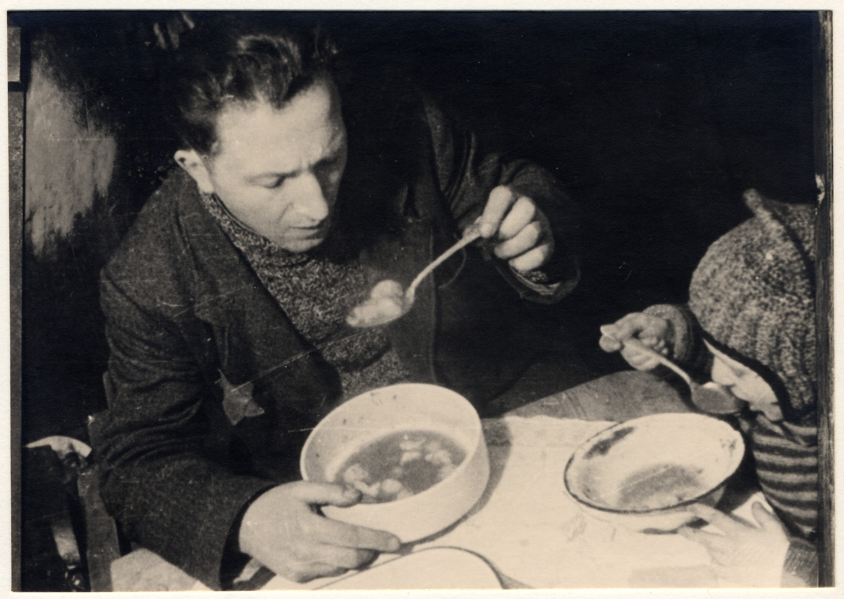 A father and son eat a bowl of soup in their kitchen in the Lodz ghetto.  Pictured are the brother-in-law and nephew of photographer Mendel Grosman.  The nephew was named Yankele Freitag.
