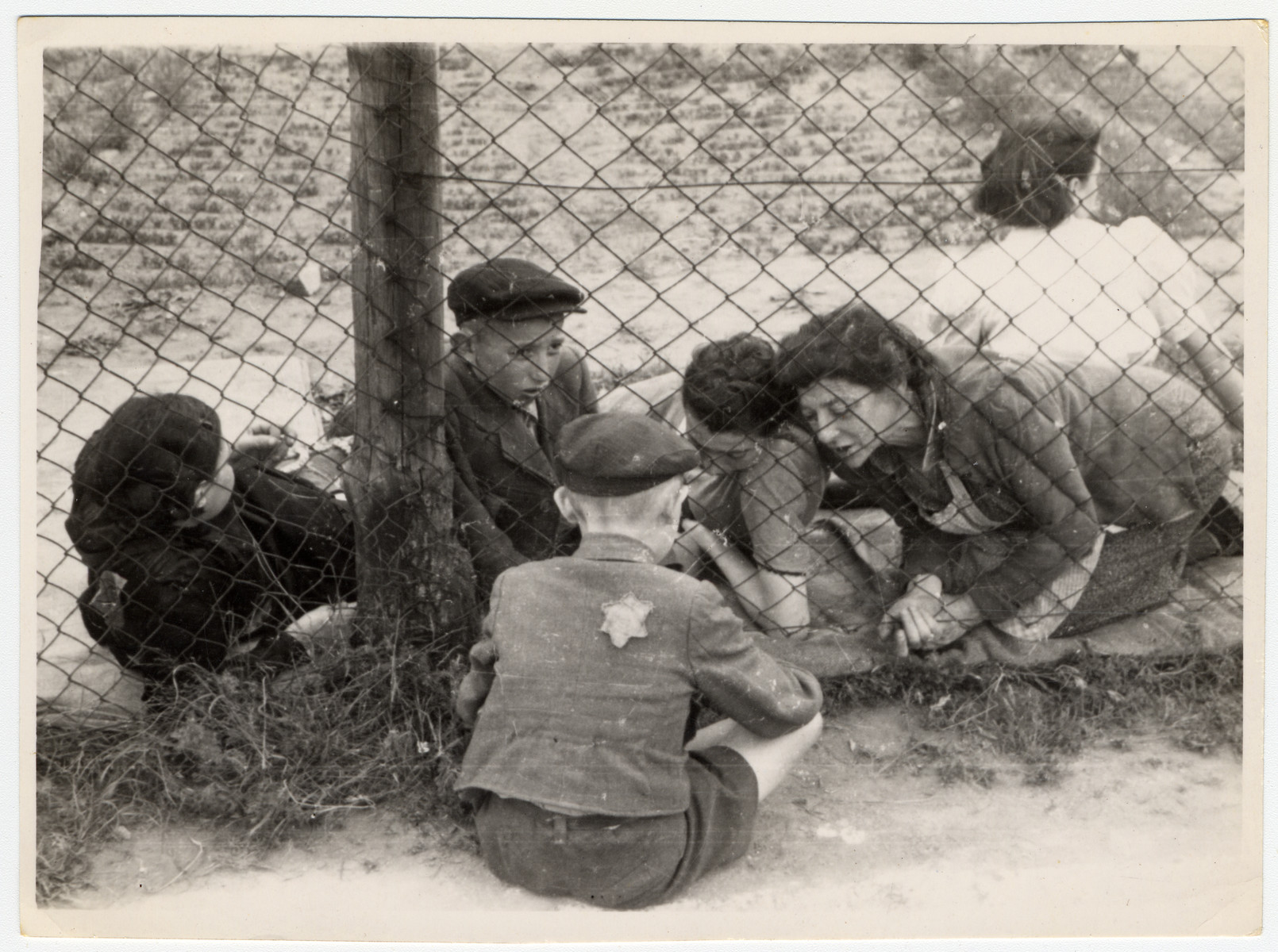 "A child who has been selected for deportation, bids farewell to his family through the wire fence of the central prison, during the ""Gehsperre"" action in the Lodz ghetto."