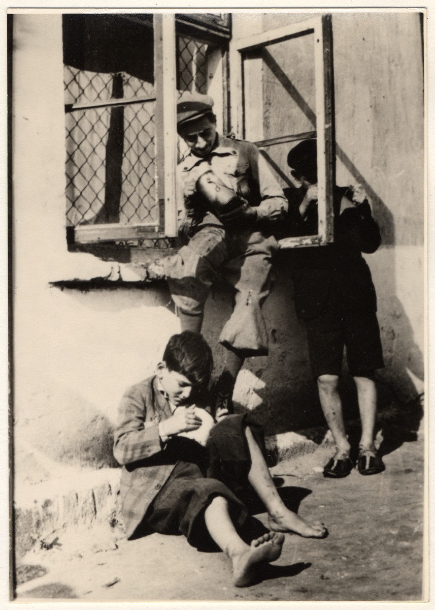 Children eating their rations in the streets of the Lodz ghetto.