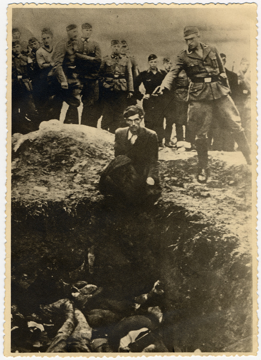 German soldiers of the Waffen-SS and the Reich Labor Service look on as a member of an Einsatzgruppe prepares to shoot a Ukrainian Jew kneeling on the edge of a mass grave filled with corpses.