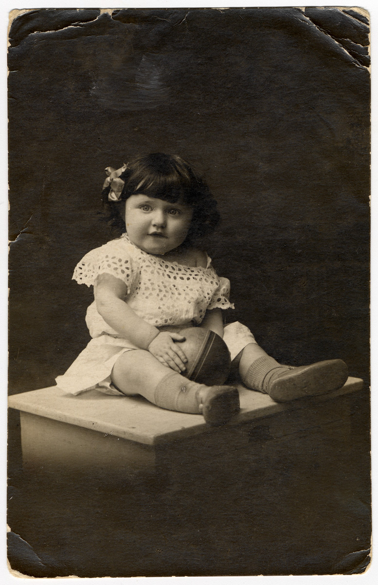 Studio portrait of a young girl holding a ball, an unidentified relative of Regina Goldberg.  Regina immigrated to the United States in 1930 and the bulk of her family in Warsaw, including five aunts, uncles and cousins perished in the Holocaust.