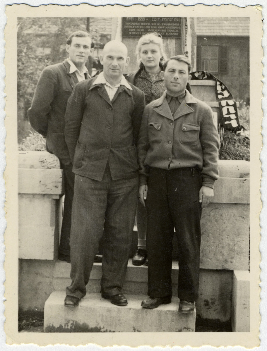 Four cousins pose in front of a memorial at the Leipheim displaced persons camp.  Standing in front are Zalman and Rubin Kaplan.  Behind them are Eli Flaks and Dwora (nee Kaplan) Flaks.