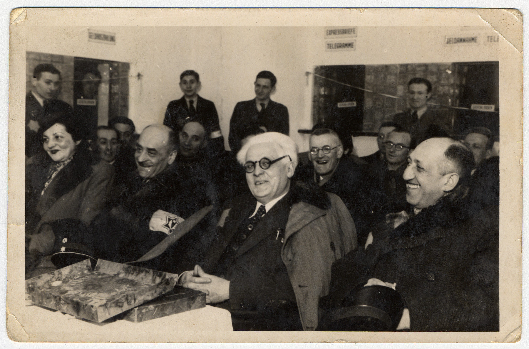 Jewish council chairman Mordechai Chaim Rumkowski (center), views a presentation album at a ceremony in the Lodz ghetto.    Pictured in front from right to left are: Dr. Leon Szykier; Mordechai Chaim Rumkowski, Leon Rozenblat and Helena Rumkowska.