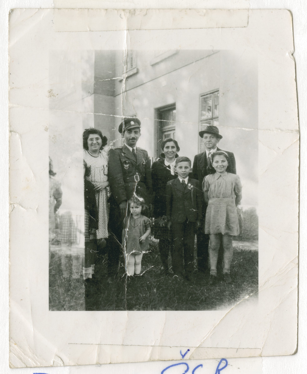 Surviving members of the Smilovic family pose outside a building in Doksy shortly after the end of World War II.  Standing from left ot right are Freidl (Freidy) Smilovic, Leo Smilovic, Feige and her husband Hanc and their three children, a girl, Lolo and Lorinka.