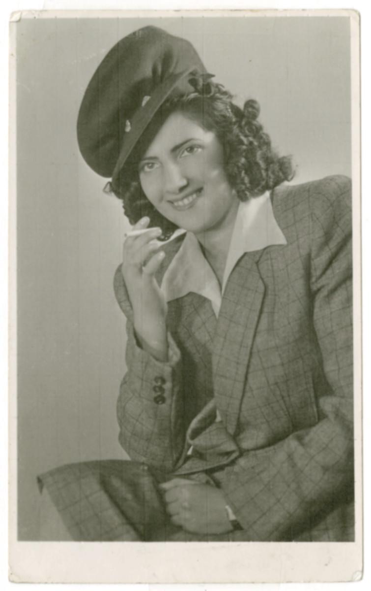 Studio portrait of Heddy Smilovic (later Spitz) smoking a cigarette.