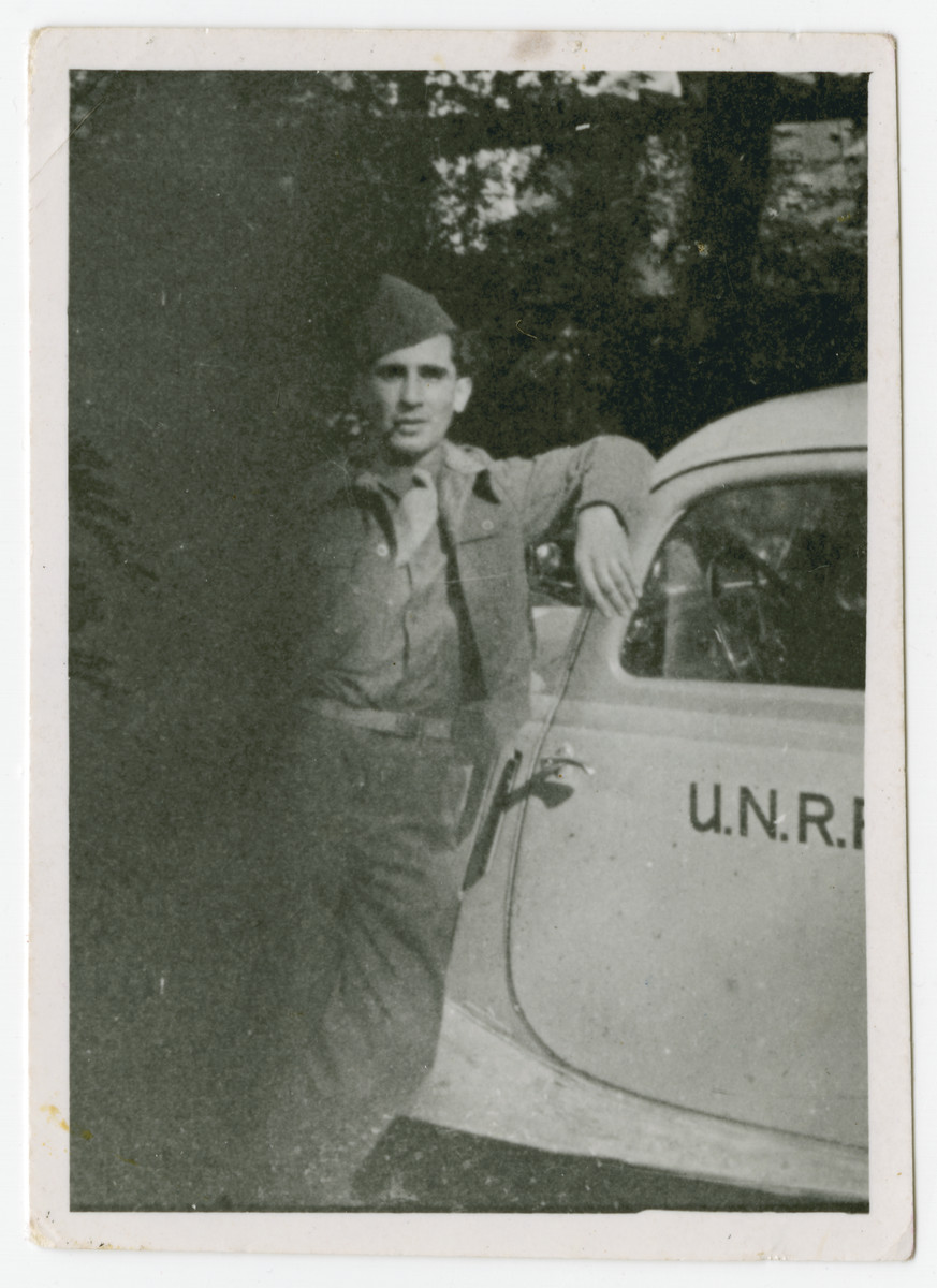 Joint Distribution Committee worker Robert Wilonsky leans against an UNRRA automobile.