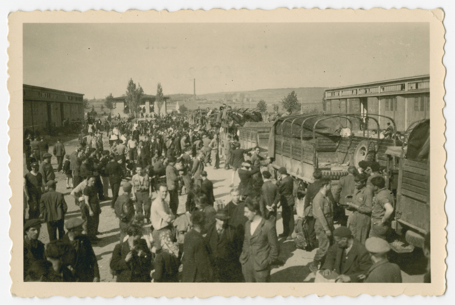 "A group of survivors get off transport trucks on arrival [probably at the [Eisenach displaced persons camp.]  The original caption reads, ""They unload and get deloused and there is much confusion and they are human beings with hopes."""