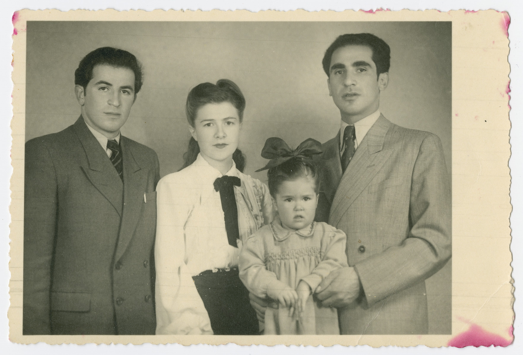 Studio portrait of the Wilonsky family taken to send to their relatives in the United States who were sponsoring their immigration so they would recognize them.  From left to right are Sam Moseson (brother-in-law of the donor), Dorothy Wilonsky, Mona Wilonsky and Robert Wilonsky.