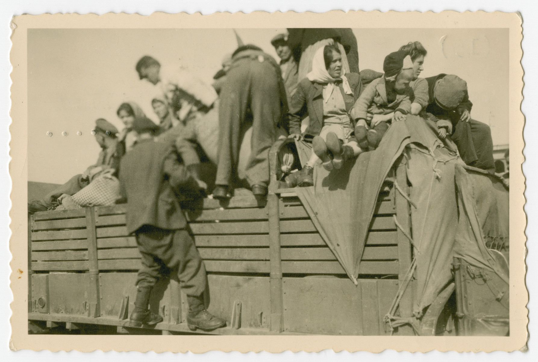"""A group of survivors climb aboard a truck transporting them out of the Buchenwald conentration camp after its liberation.  The original caption reads, """"get aboard and some are killed in the process and others..."""""""