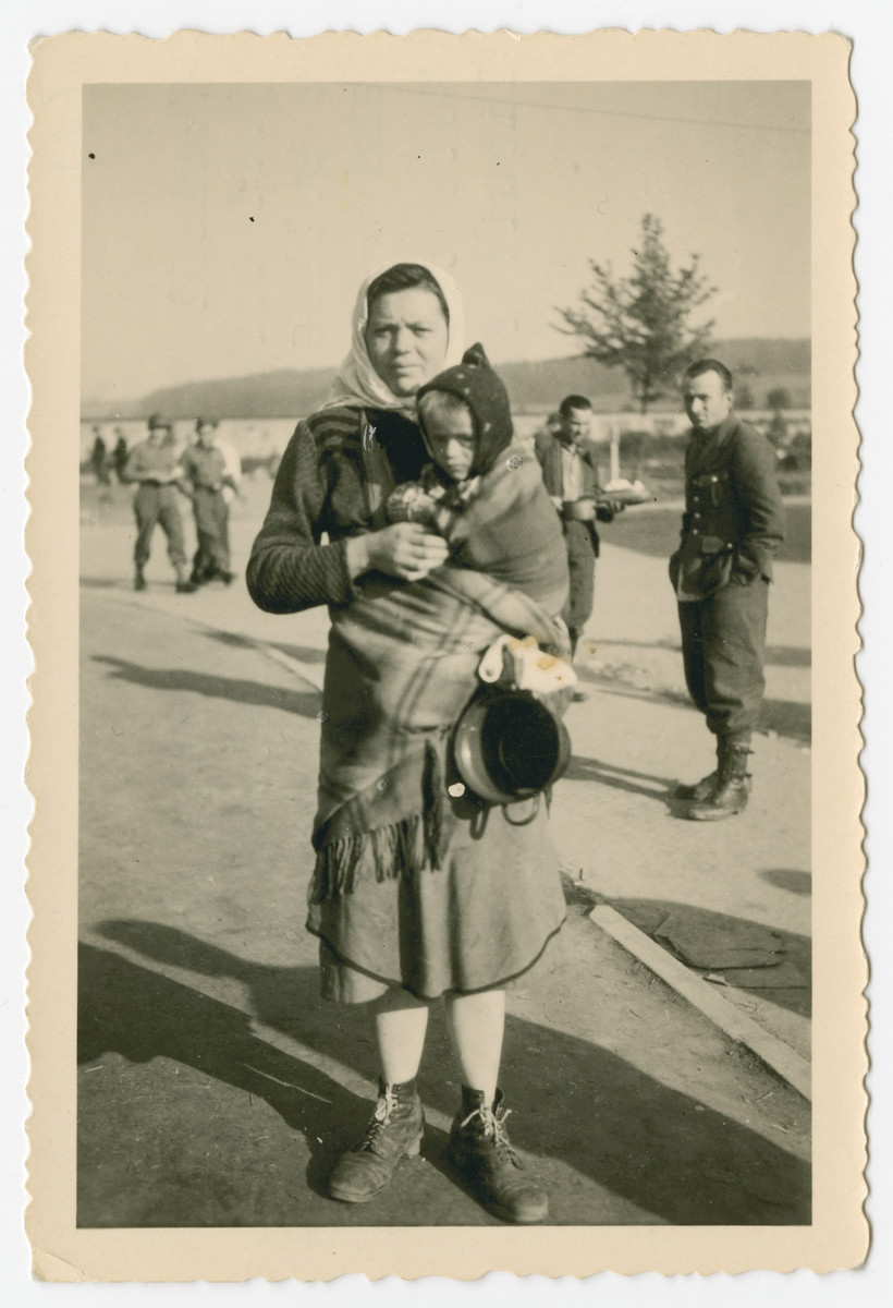 "Portrait of a Russian woman carrying a child at a collection point for a DP camp.  The photograph's original caption reads, ""Typical Russian mother with child just before we recieved them at a collecting point. Note the shoes she wears - if lucky. Note the container she hold for liquid food."""